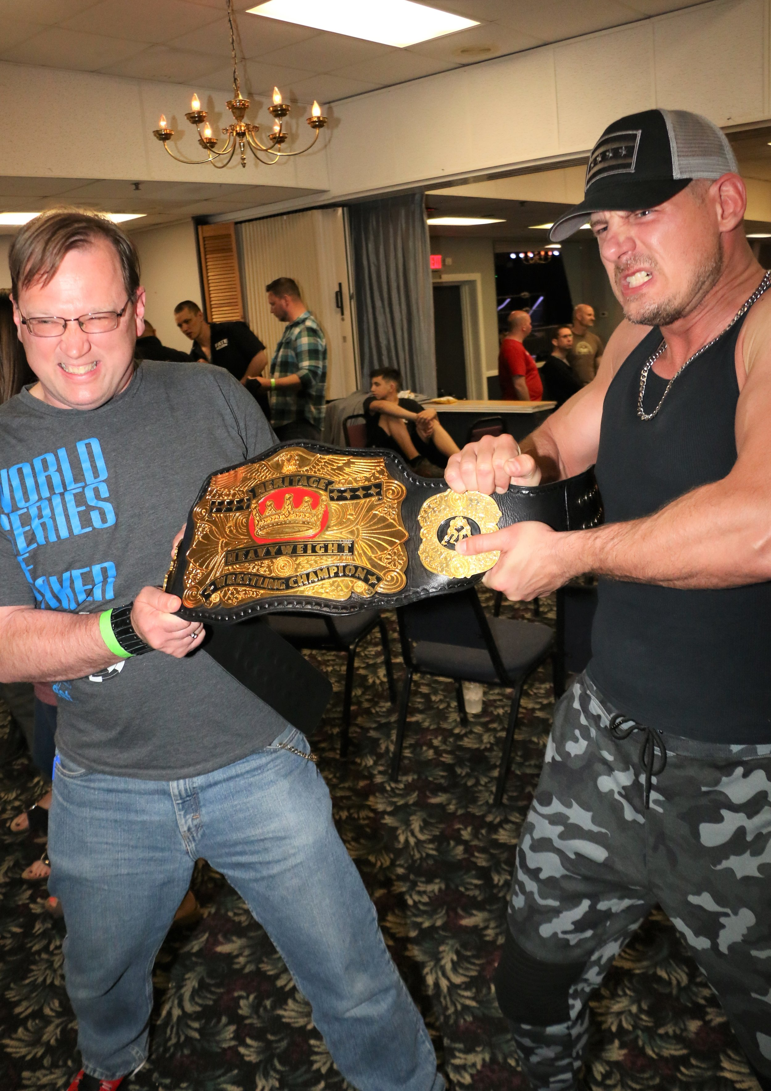 New Midwest Heritage Champion Eric Priest and a fan play tug-of-war with the title after the show.