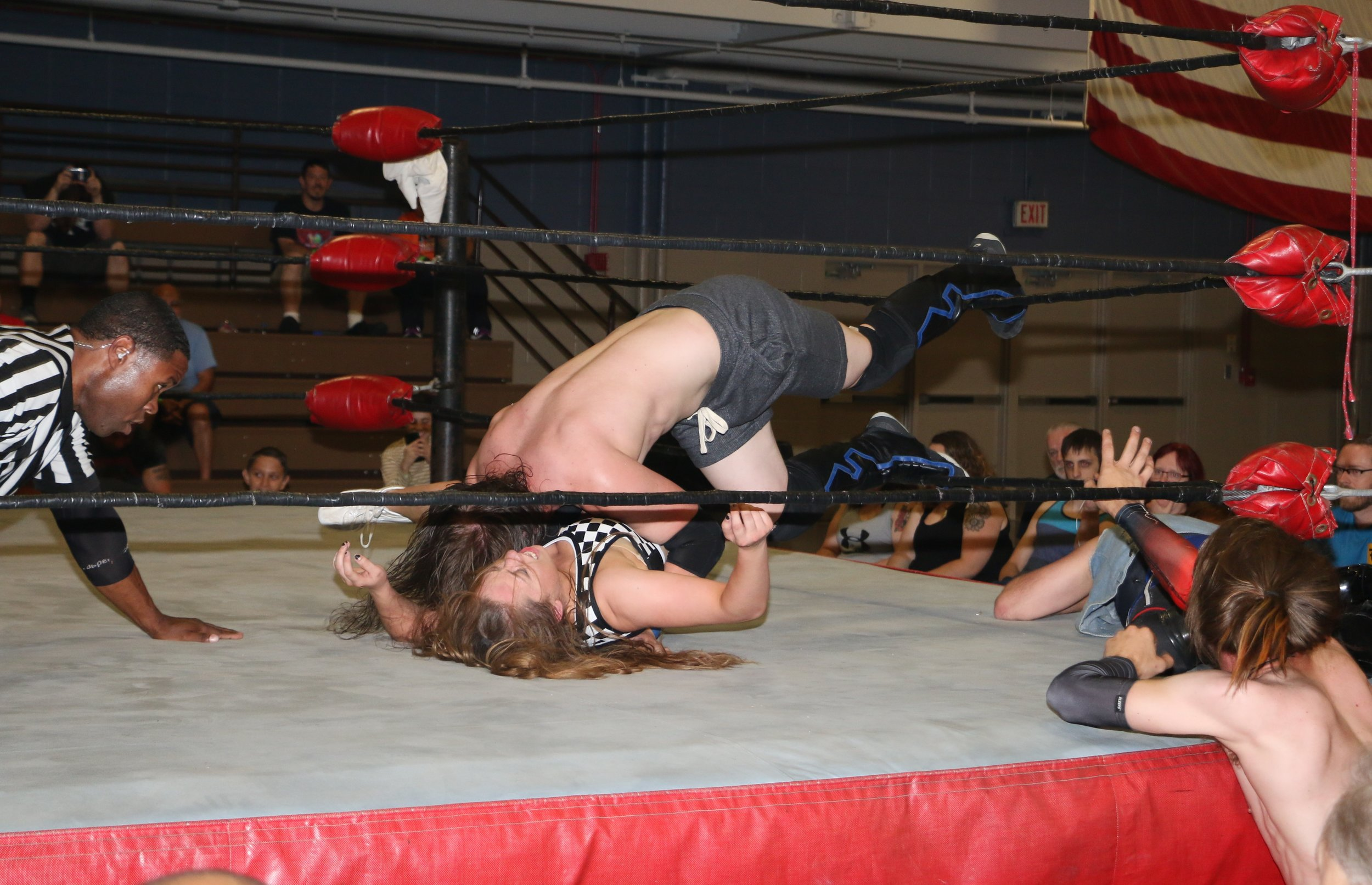"""Hipster Hunk"" Aaron Arsenal pins Missa Kate with his feet on the ropes."