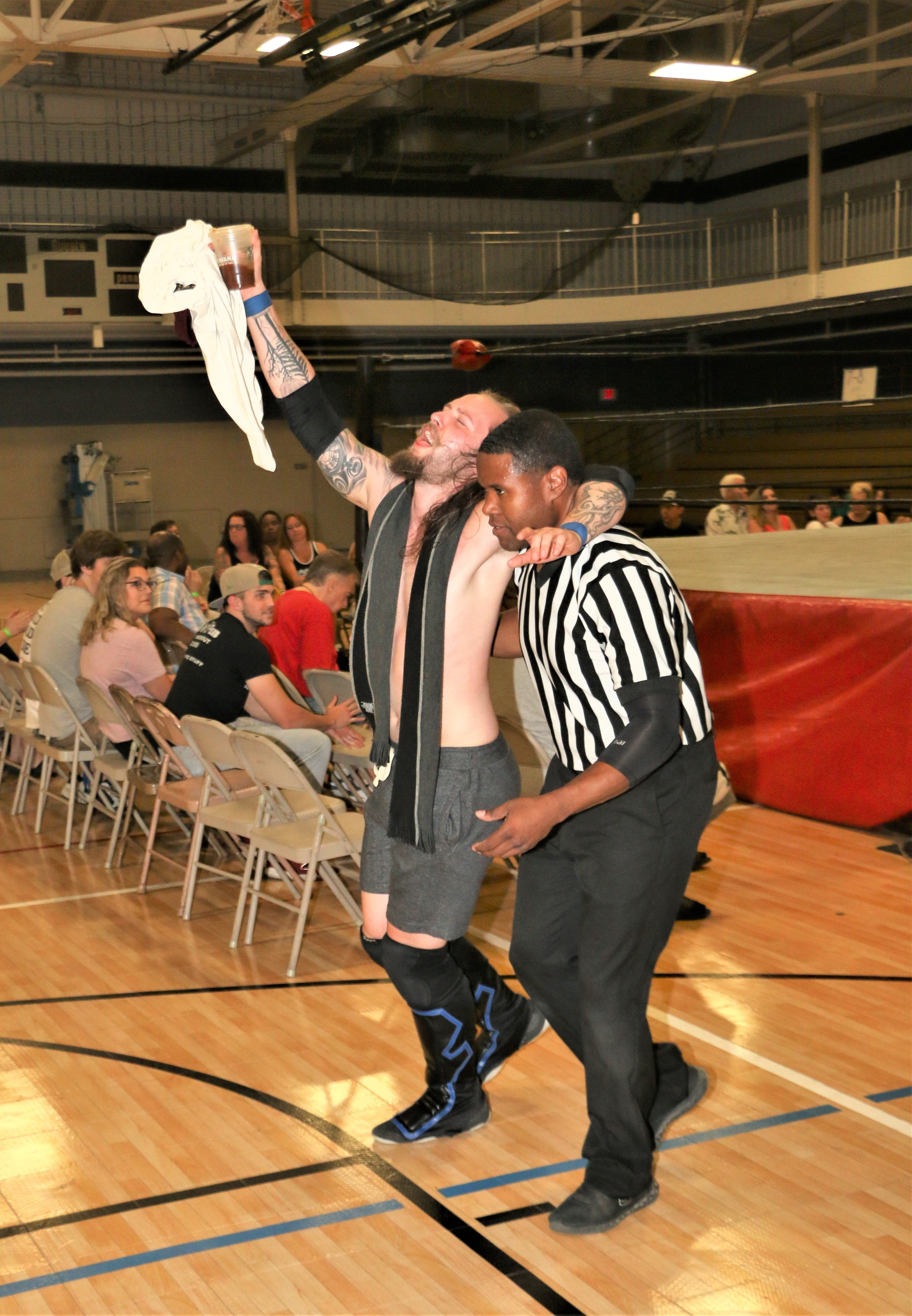 Referee Jessie Bush helps Aaron Arsenal out of the ring.