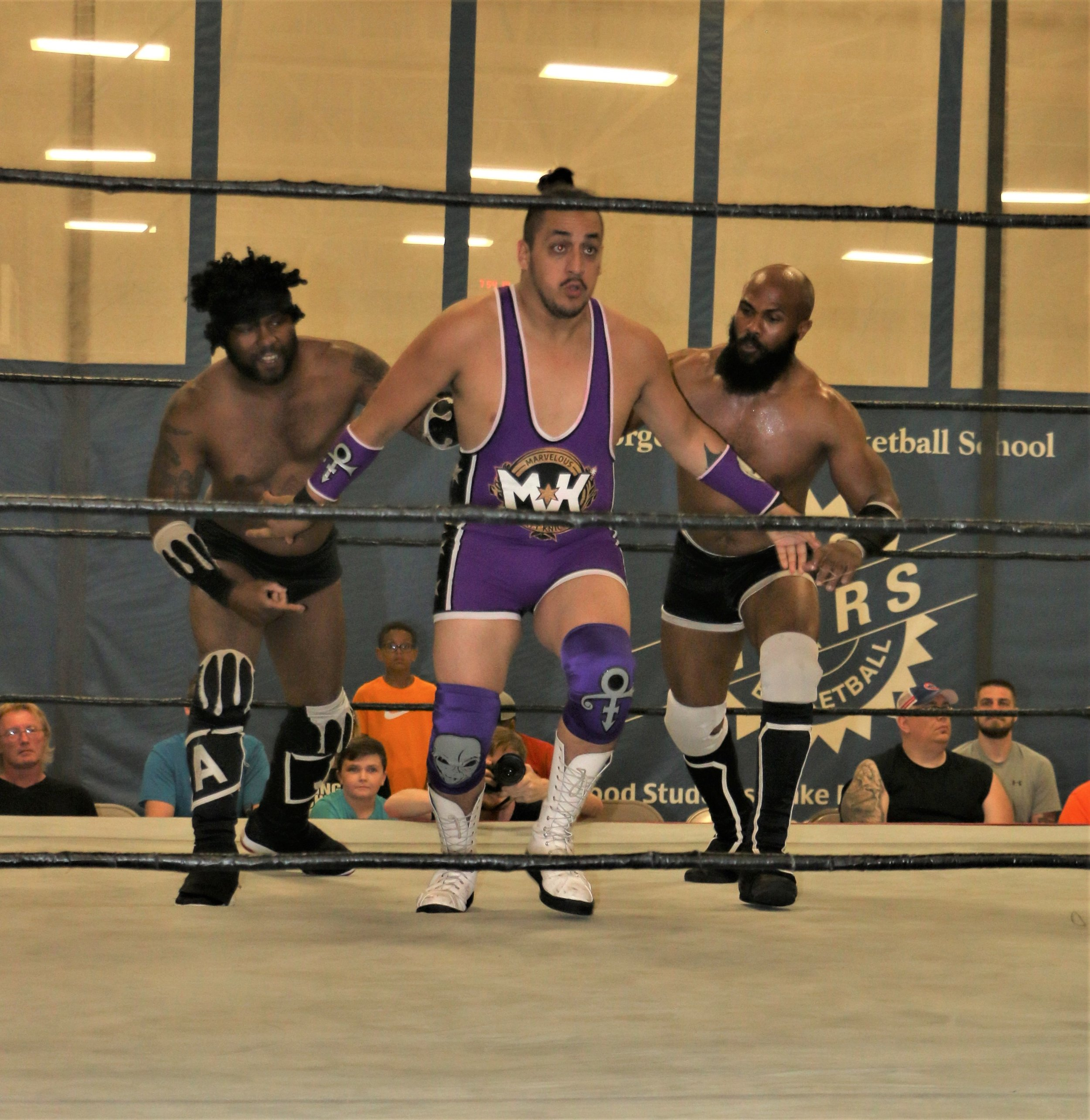 Acid Jaz, left, and Bryce Benjamin, right, whip Matt Knicks into the ropes during their tag-team match.