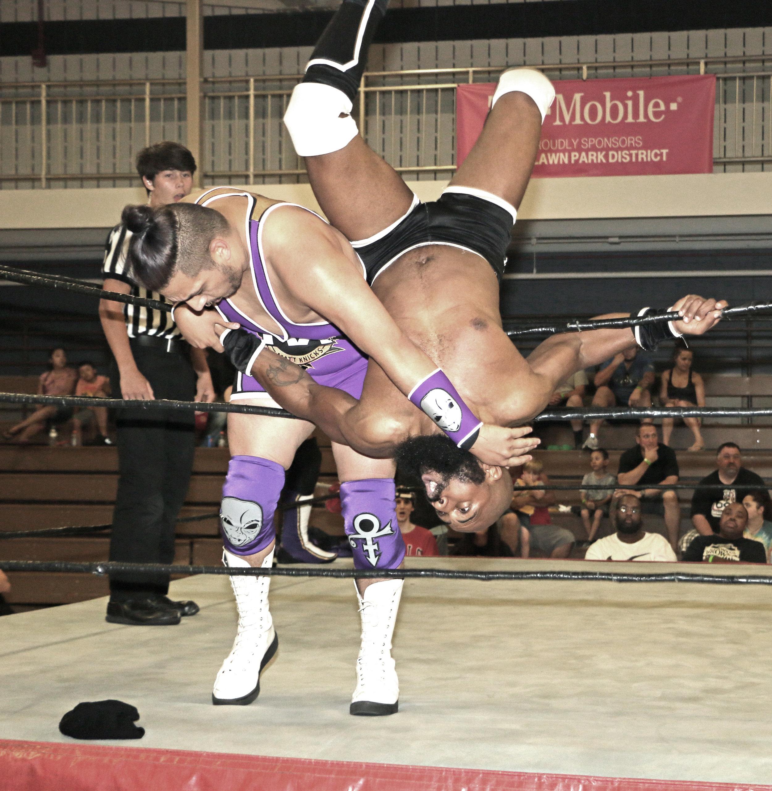 Matt Knicks sends Bryce Benjamin outside the ring.