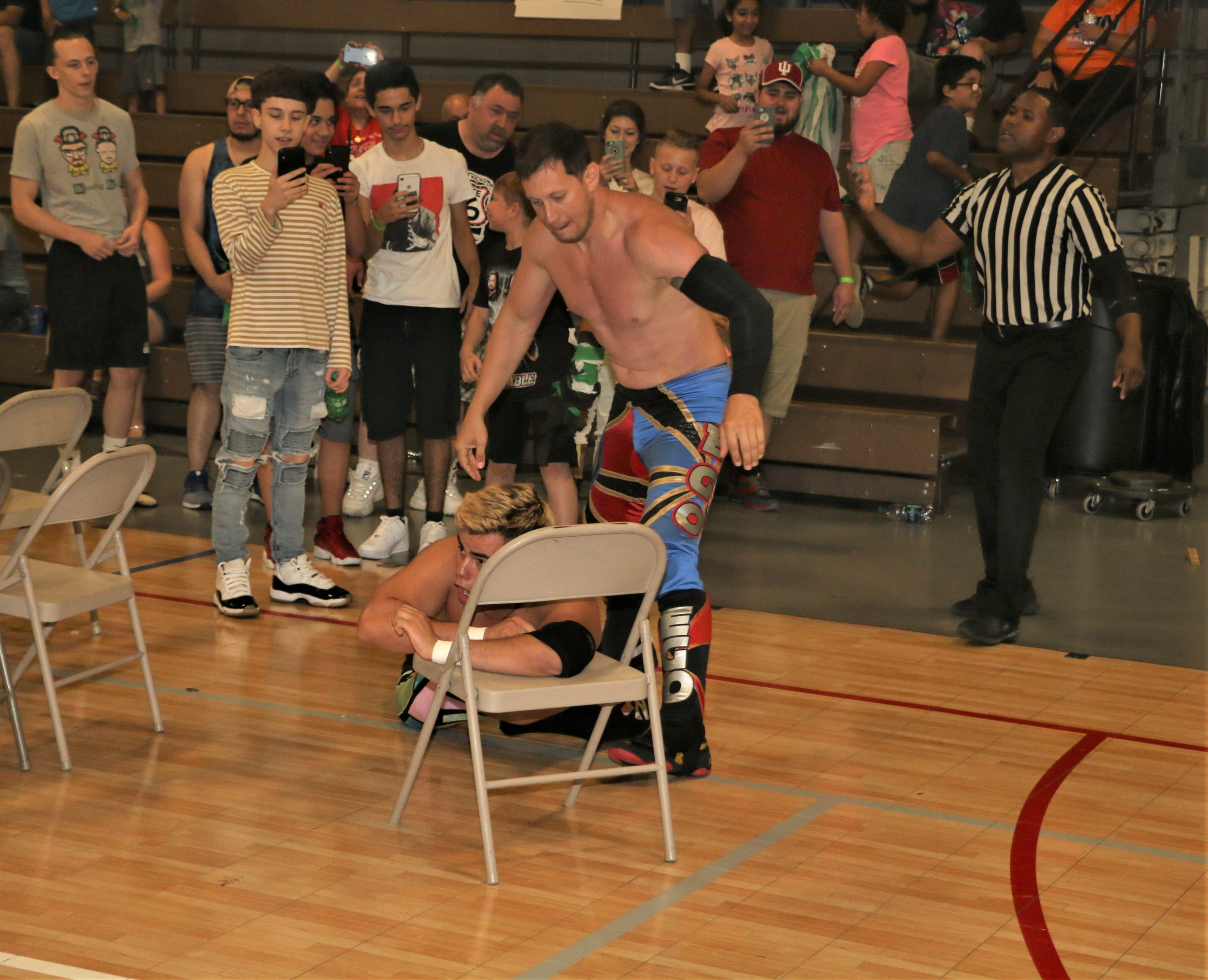 """Robert """"Ego"""" Anthony sets up Joe Alonzo on a chair at ringside."""