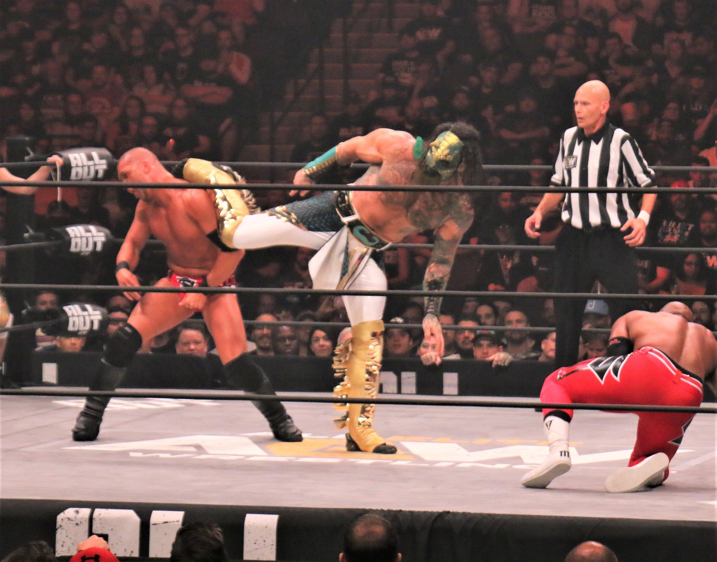 Luchasaurus kicks Frankie Kazarian in the head.