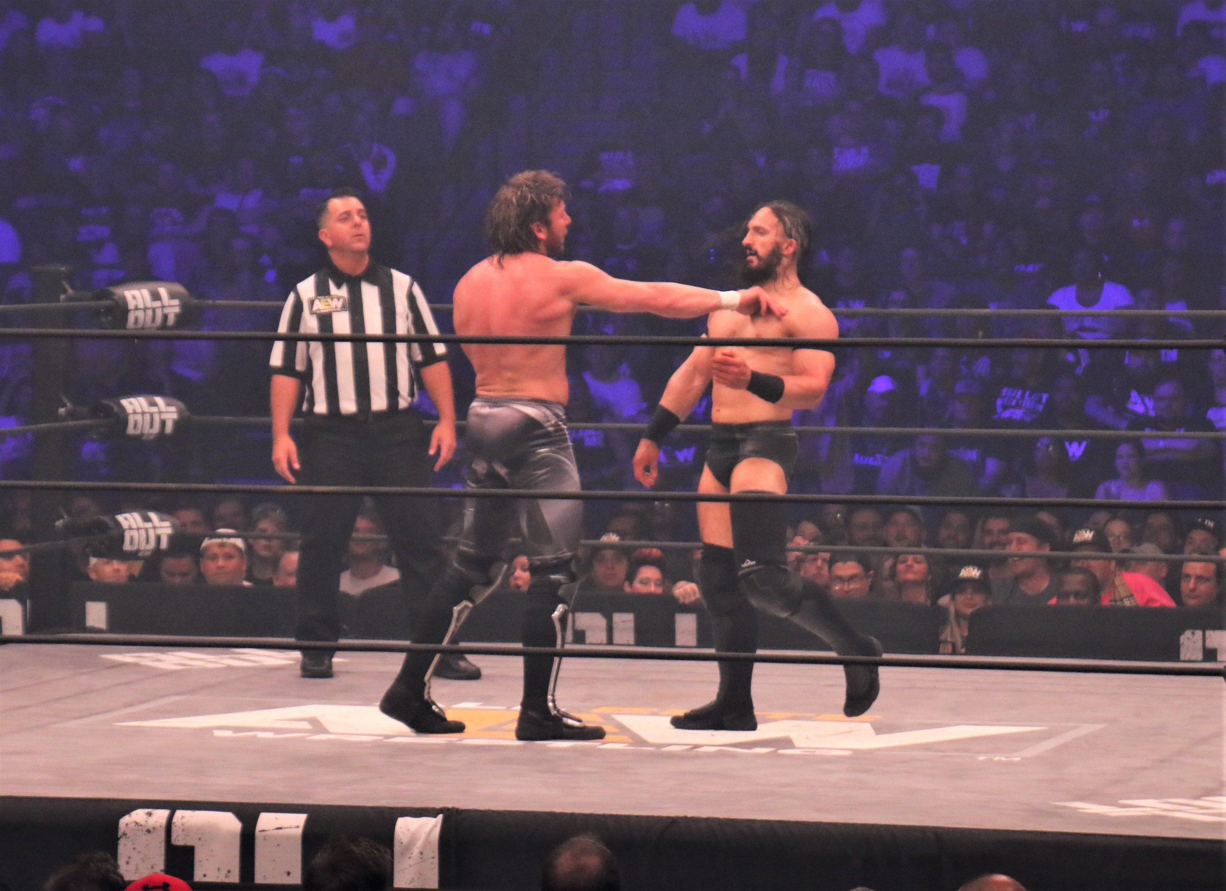 Kenny Omega faces off with PAC.
