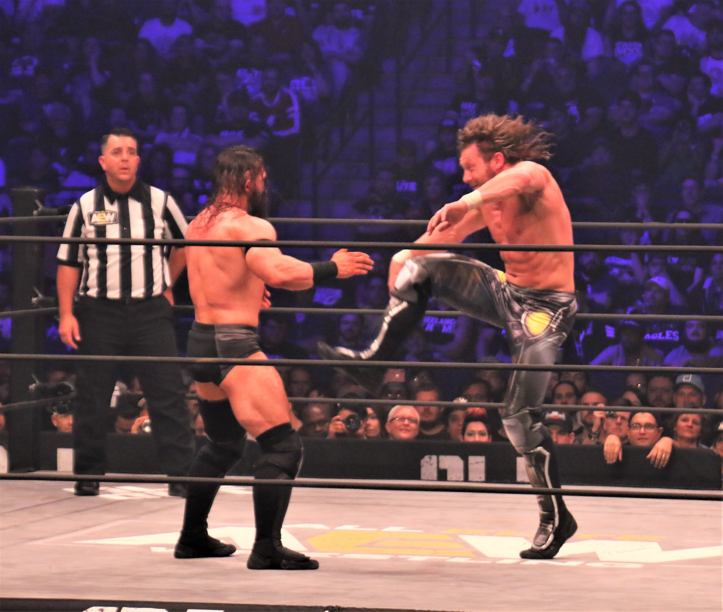 Kenny Omega delivers a kick to PAC.