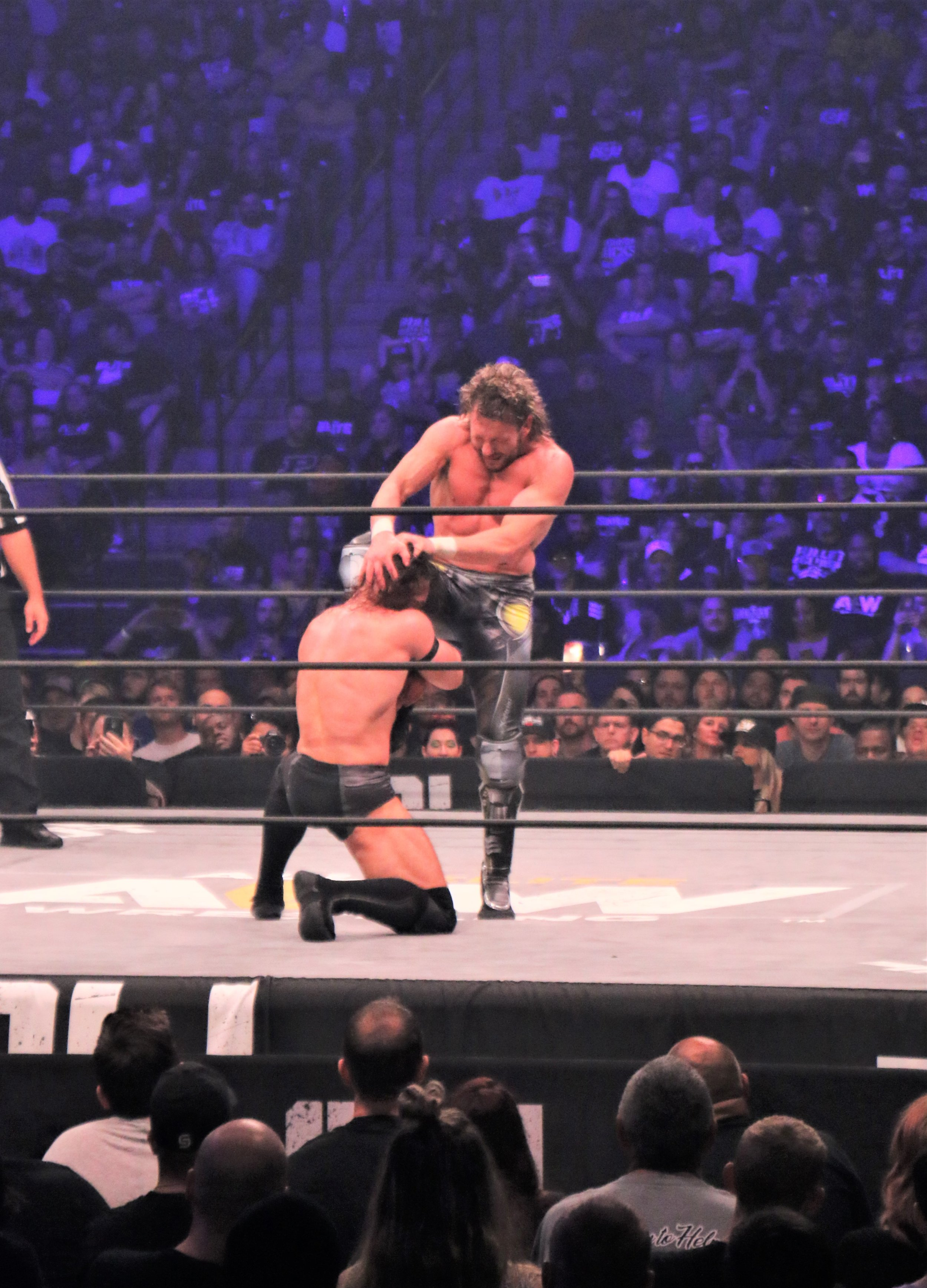 Kenny Omega attempts a knee strike on PAC.