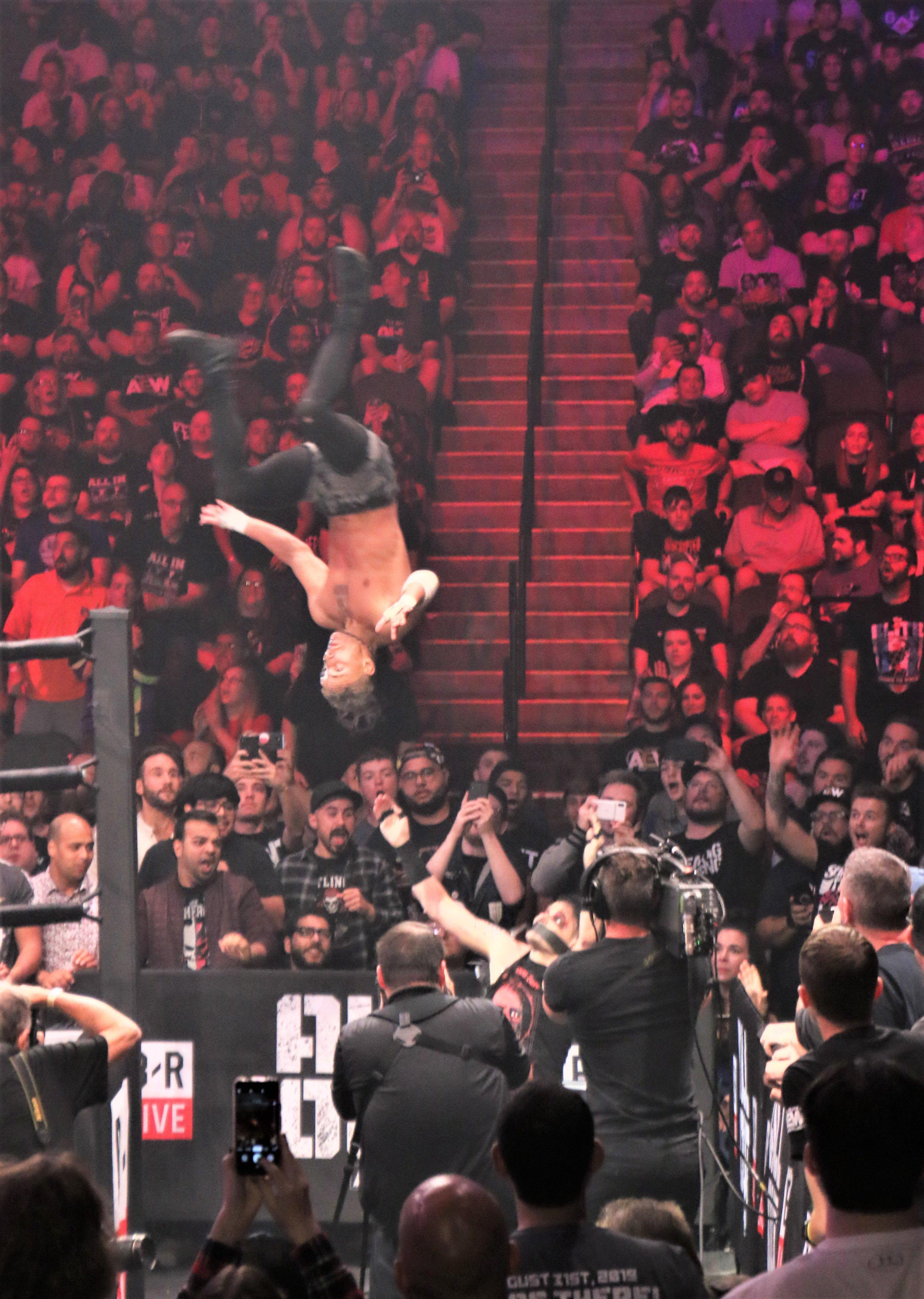 Darby Allin flies toward Jimmy Havoc on the outside.