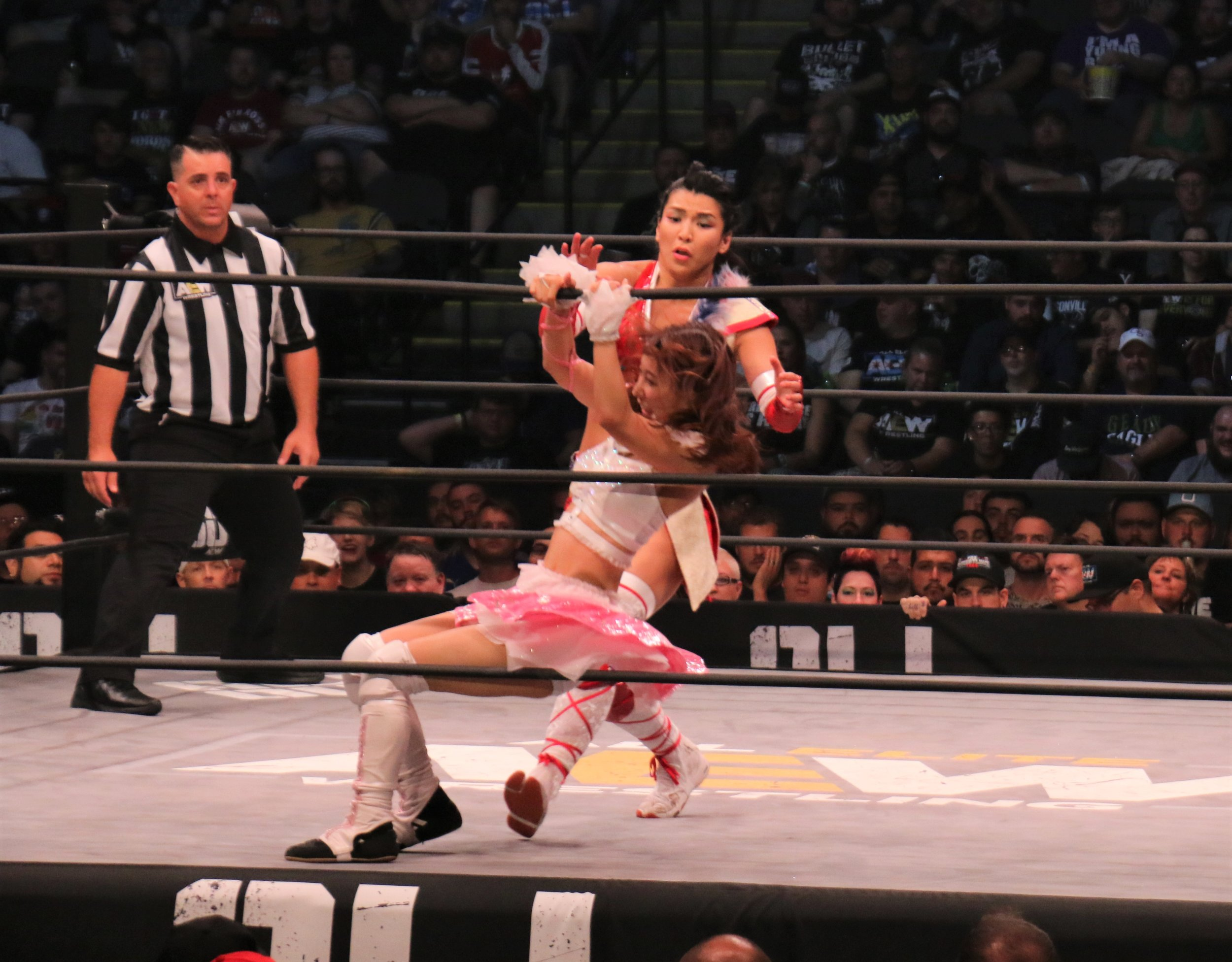 Riho pulls the top rope as Hikaru Shida charges toward her.