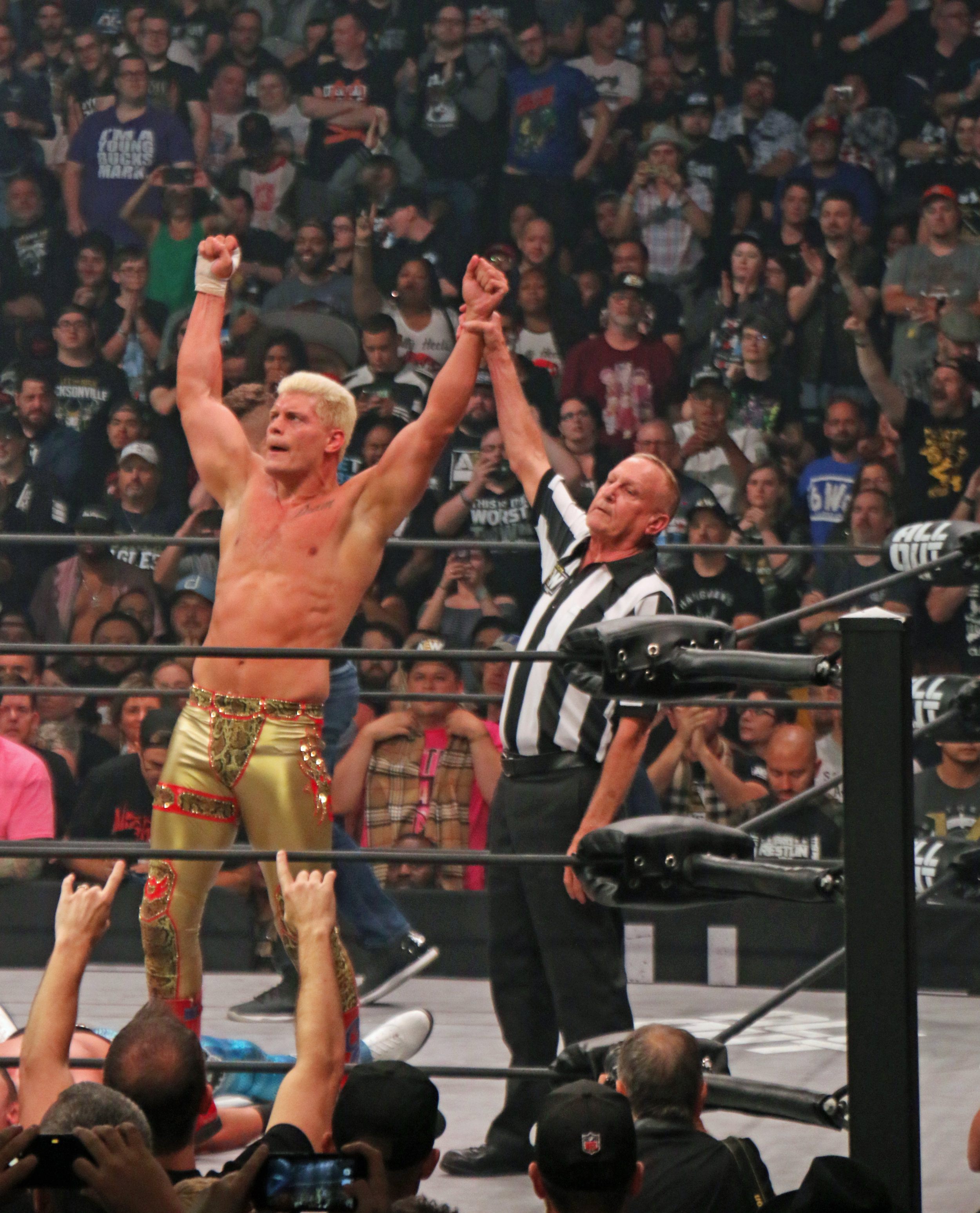 Cody gets his hand raised by Earl Hebner after defeating Shawn Spears.