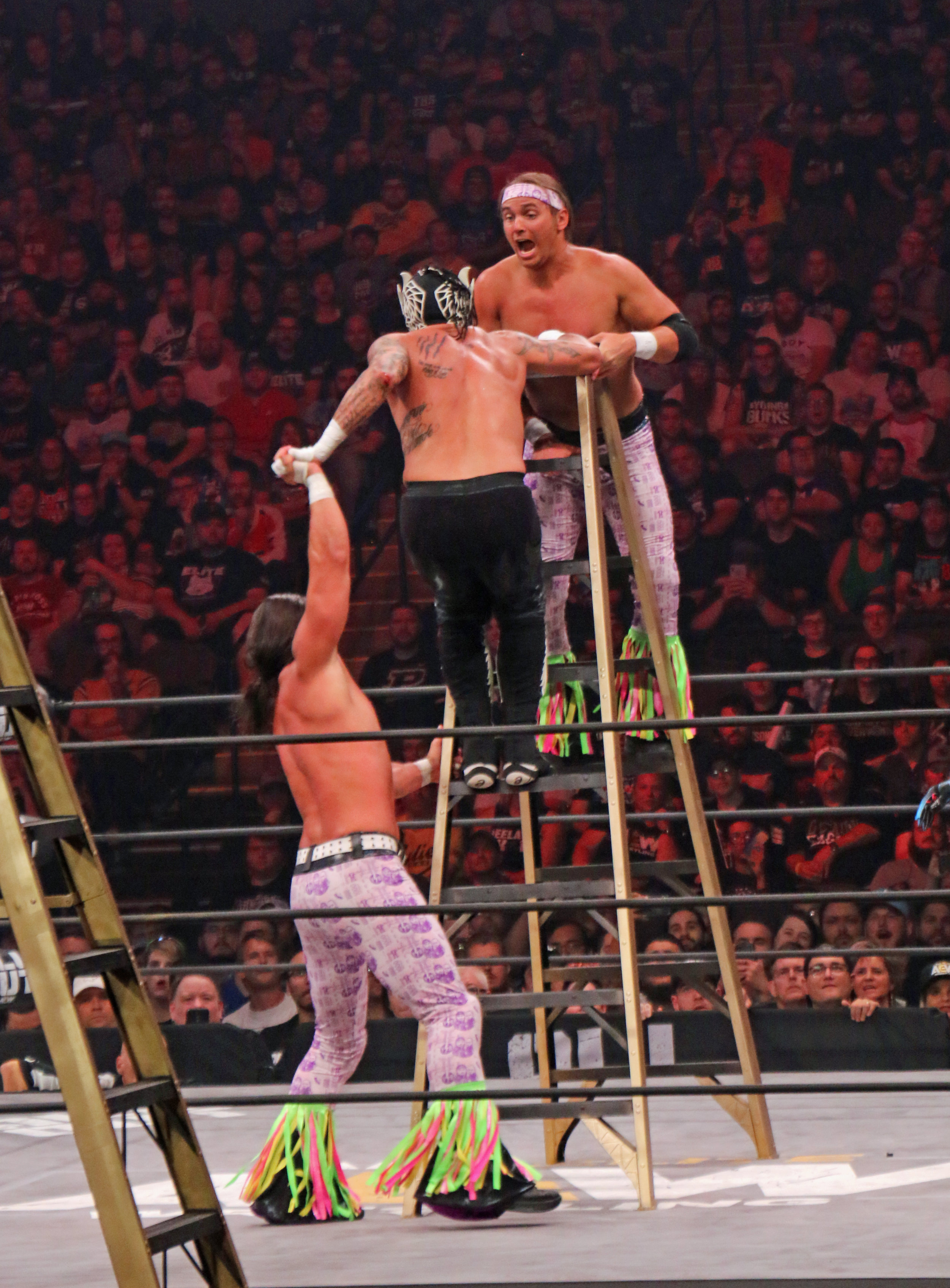 "Rey Fenix caught in the middle of the Young Bucks during the ""Escalera de la Muerte"" ladder match."