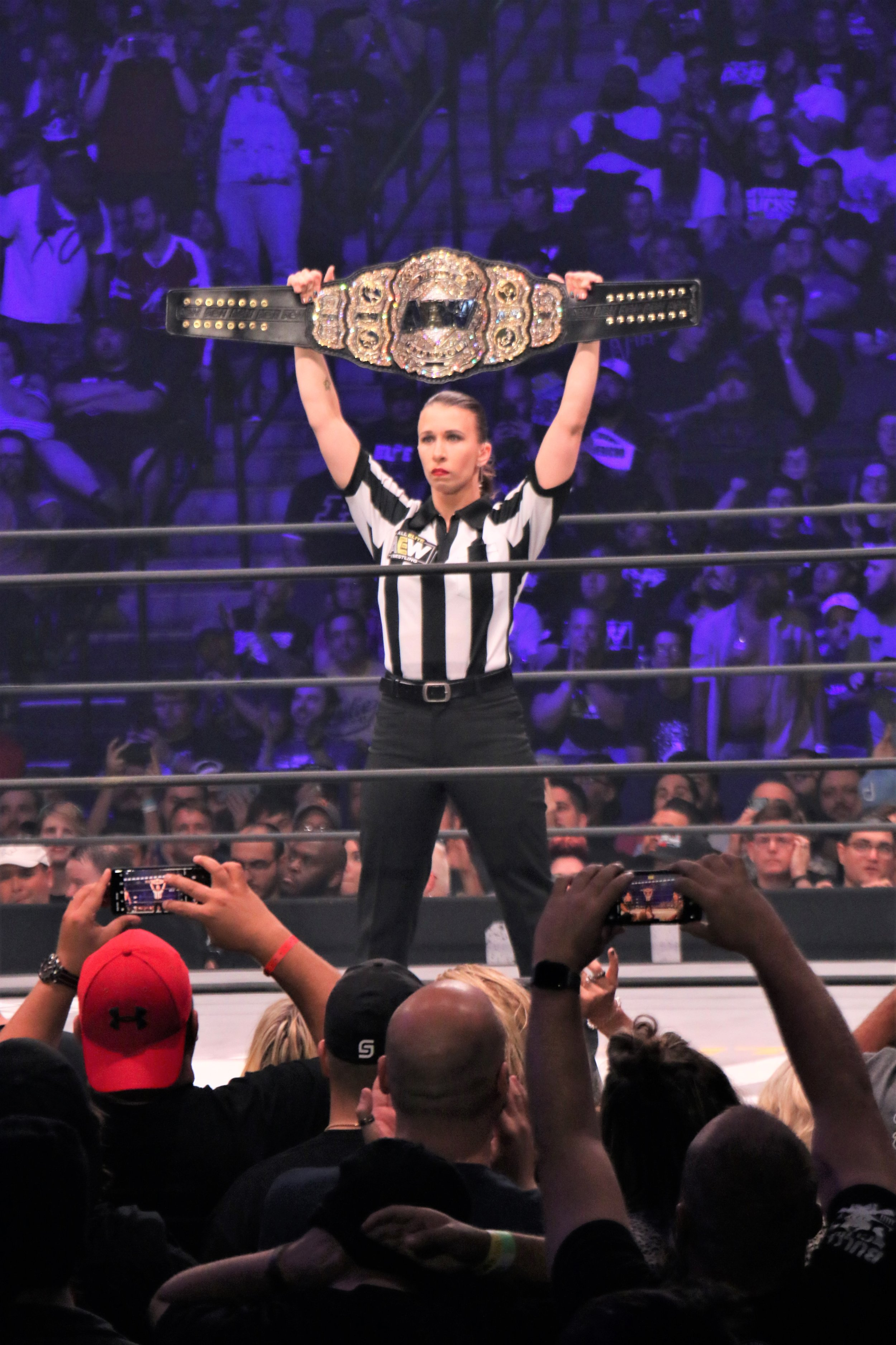 Referee Aubrey Edwards holds up the AEW Championship.