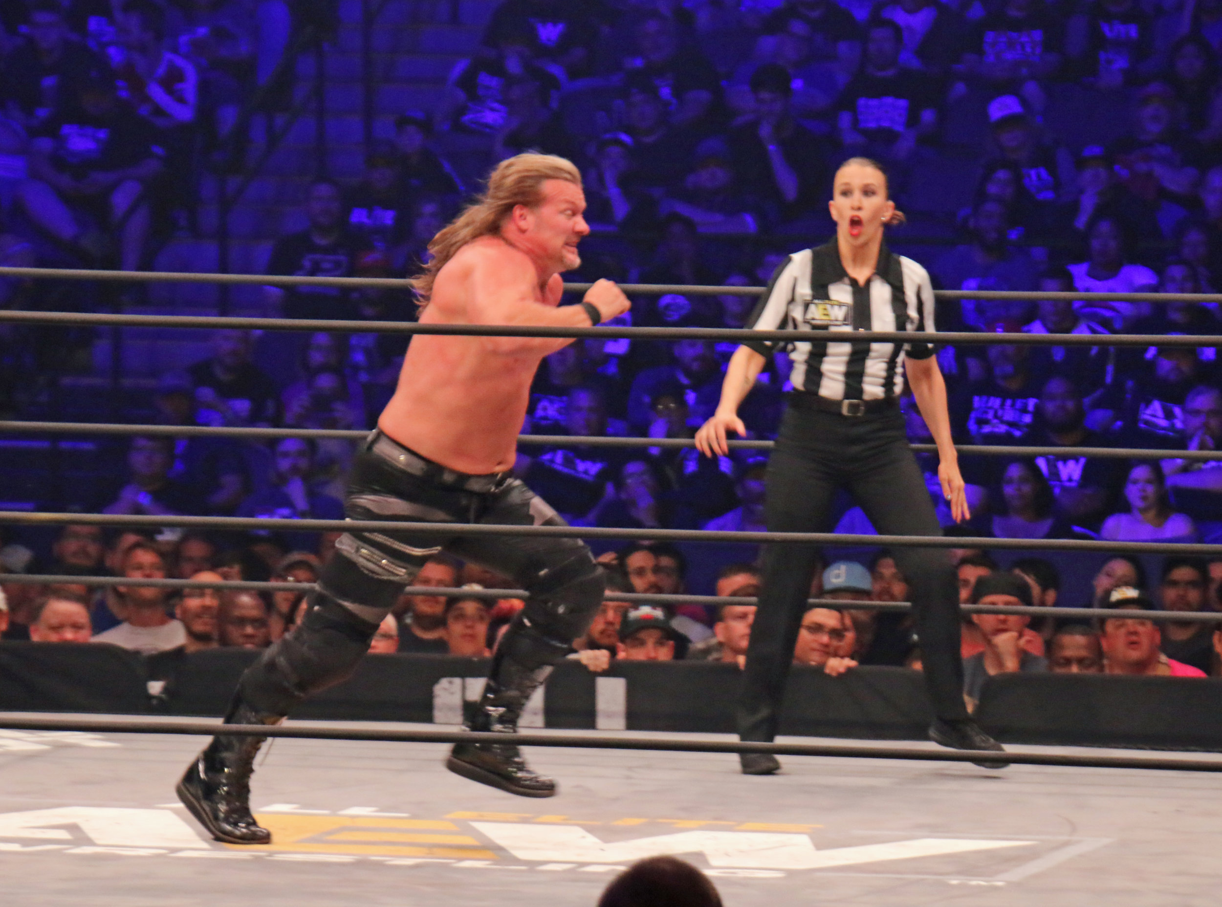 Chris Jericho charges toward Hangman Page (not pictured) as referee Aubrey Edwards reacts.