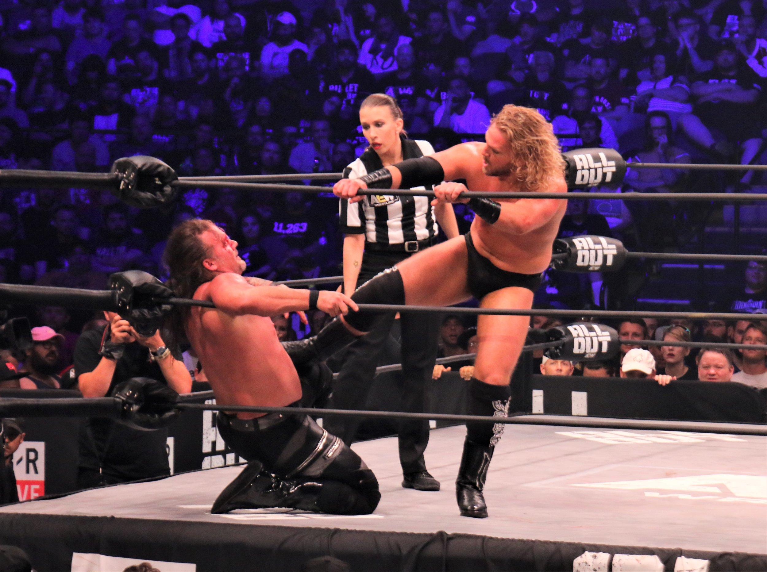 Hangman Page kicks Chris Jericho in the corner.