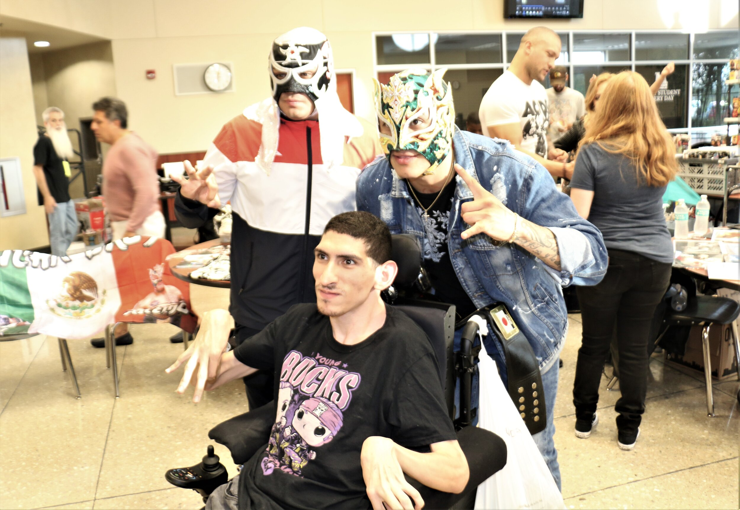 Wrestling fan Niko poses with Penta El 0M, left, and Fenix at the Warrior Wrestling 6 VIP Fan Fest.