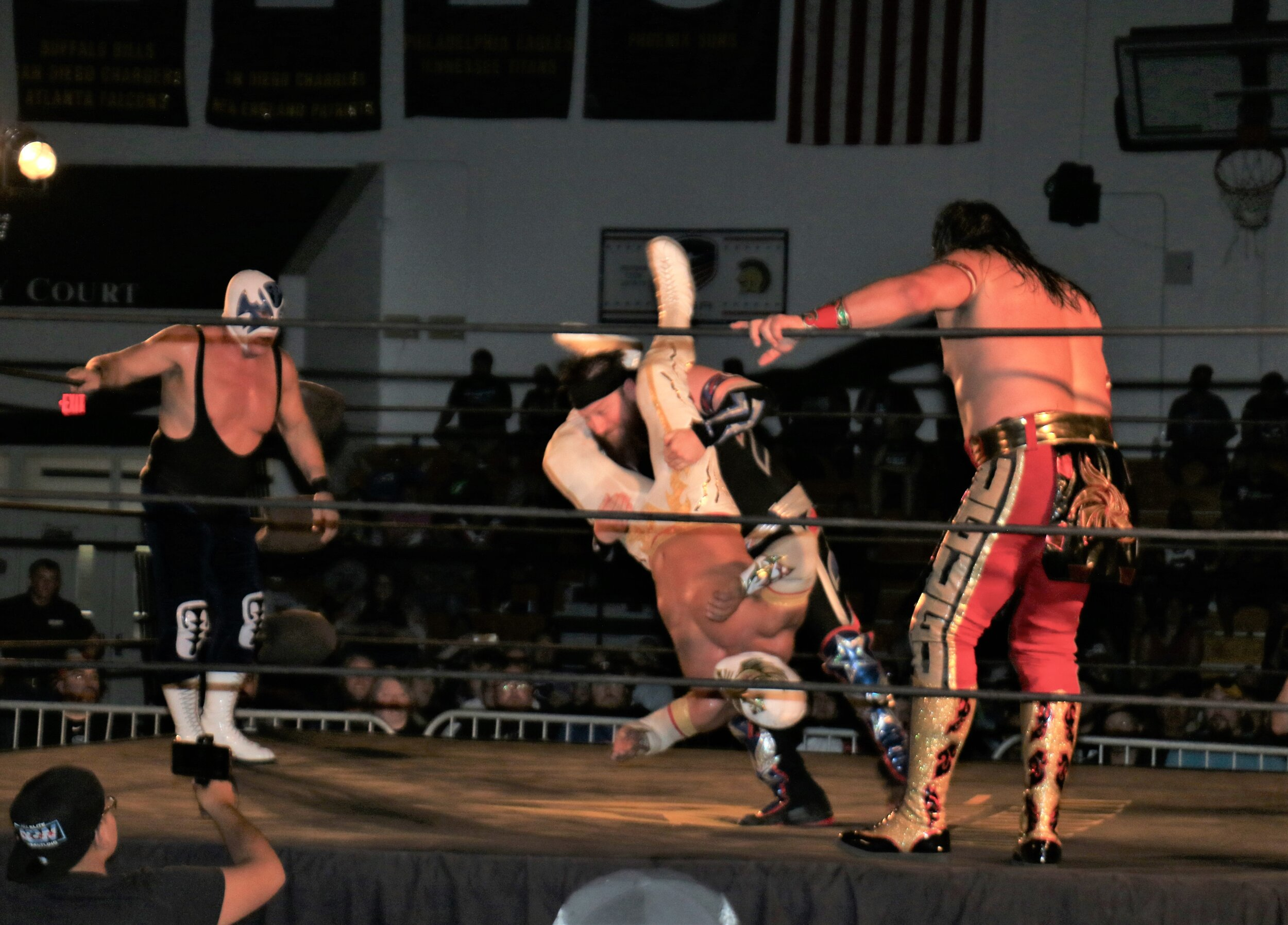 Caristico, center, takes over Gringo Loco, who stormed the ring to attack the luchadors.