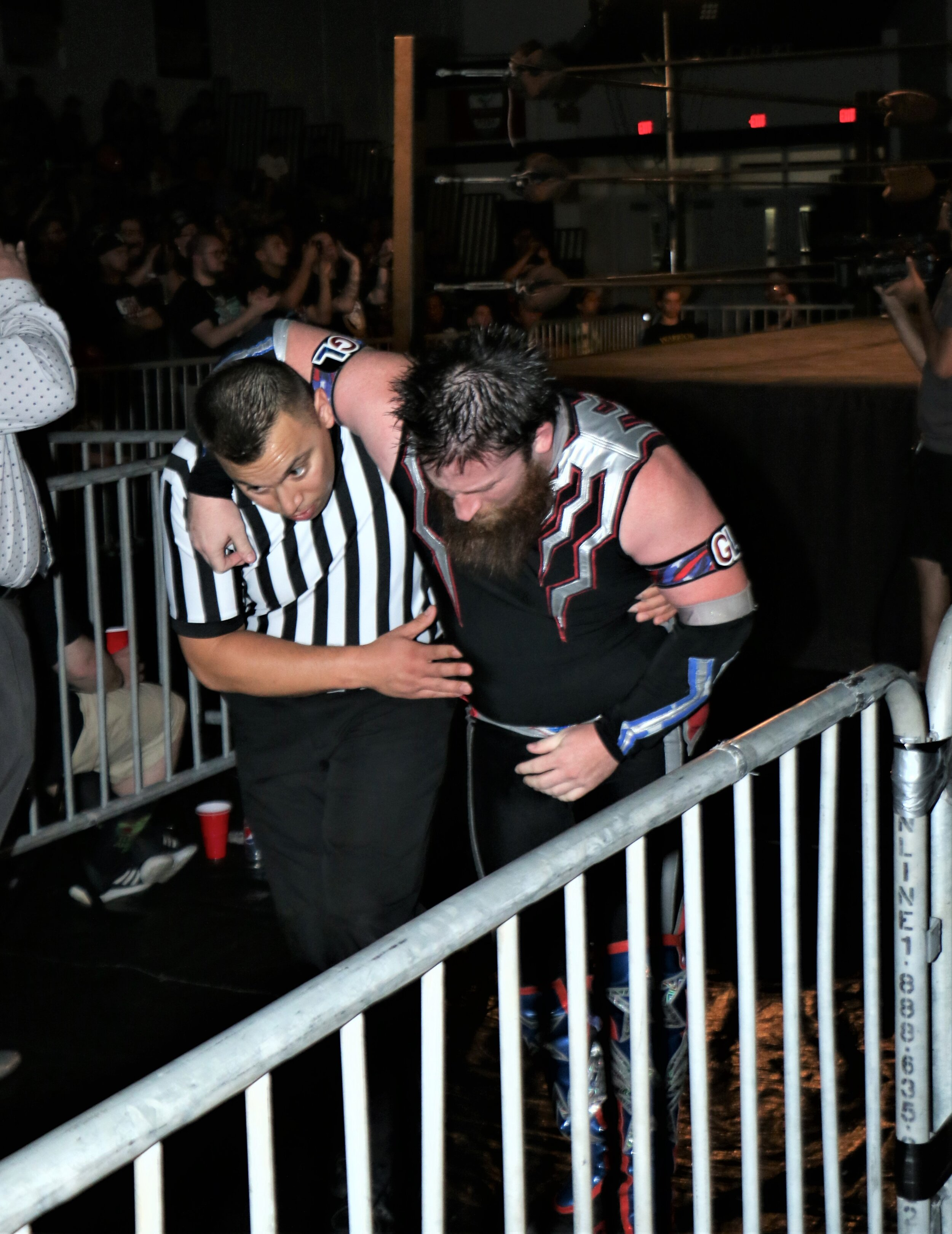 Referee Jeremy Tillema helps Gringo Loco to the back.