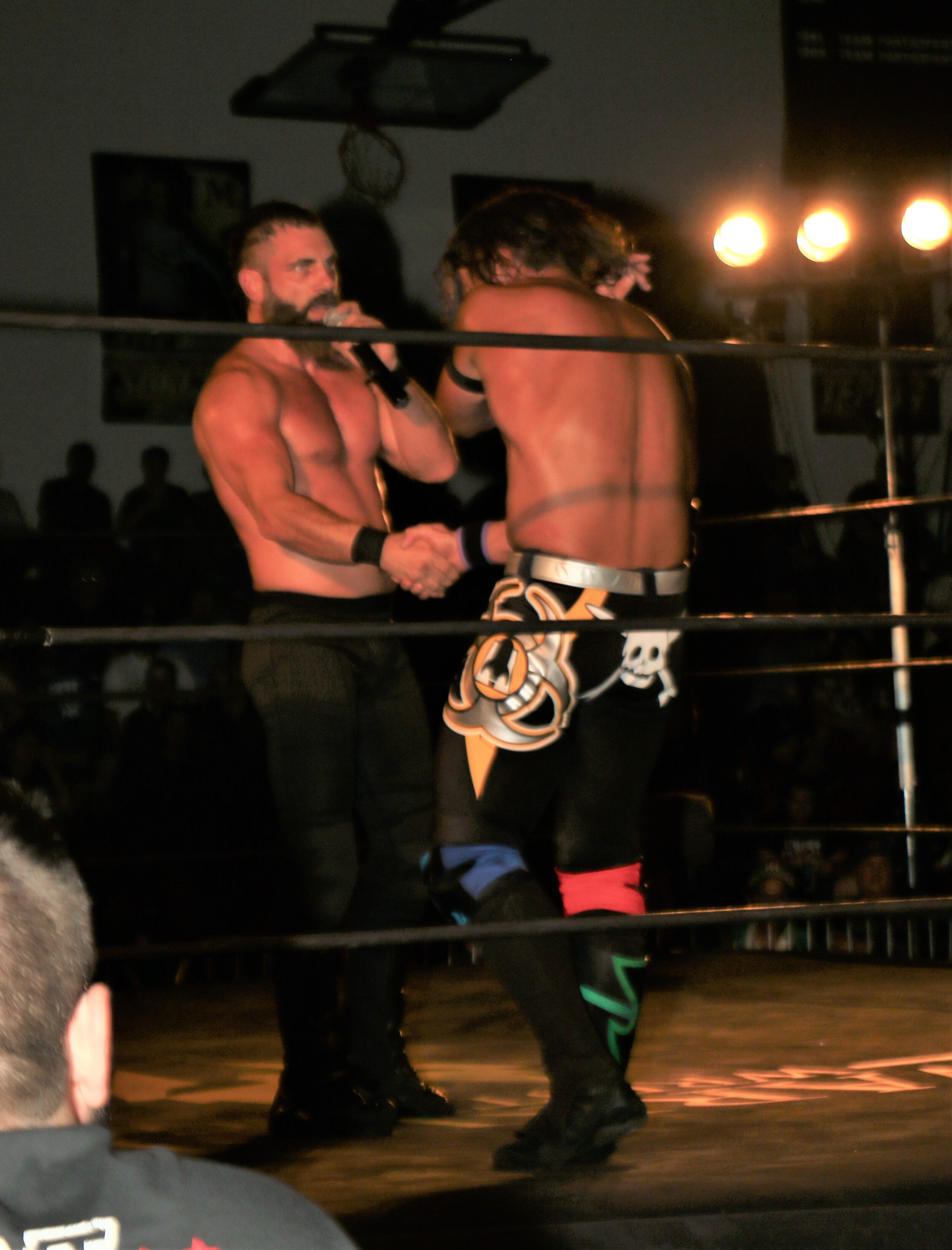 Austin Aries, left, shakes the hand of Alex Shelley following Aries' victory.
