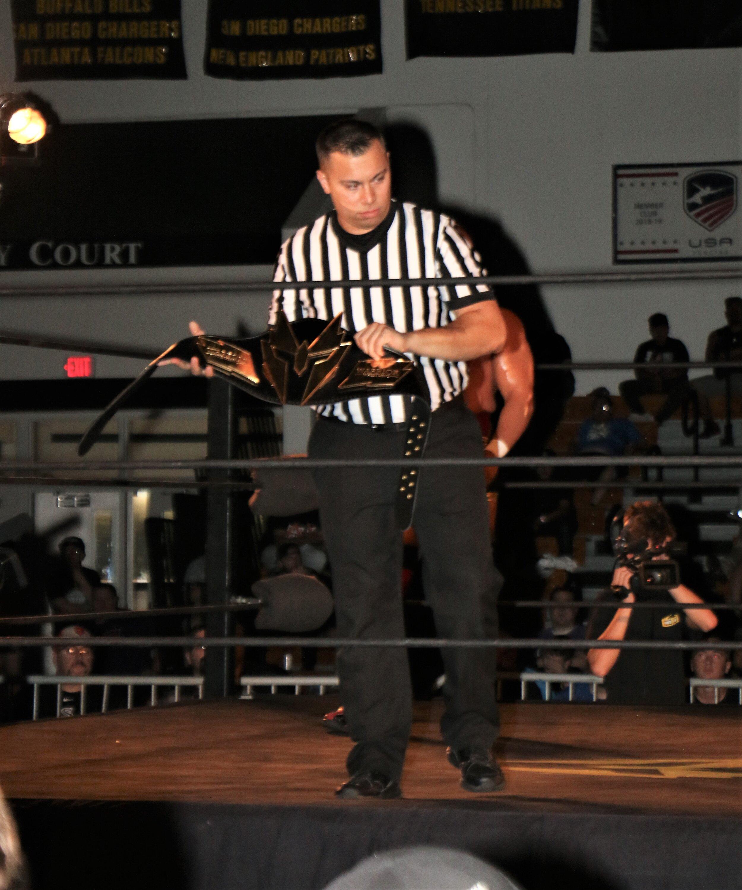 Referee Jeremy Tillema displays the Warrior Wrestling Championship belt.