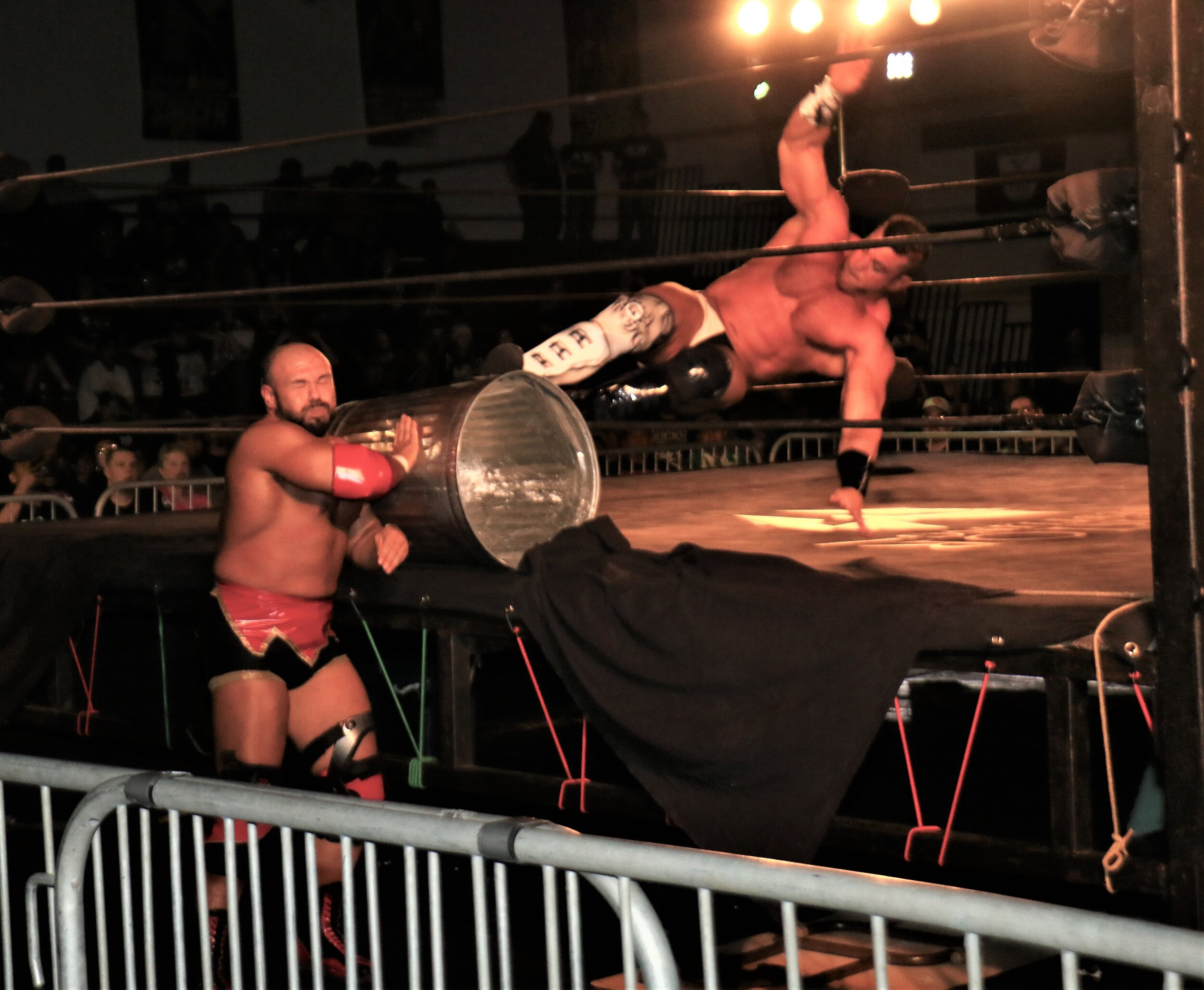 Brian Cage kicks the garbage can into Michael Elgin.