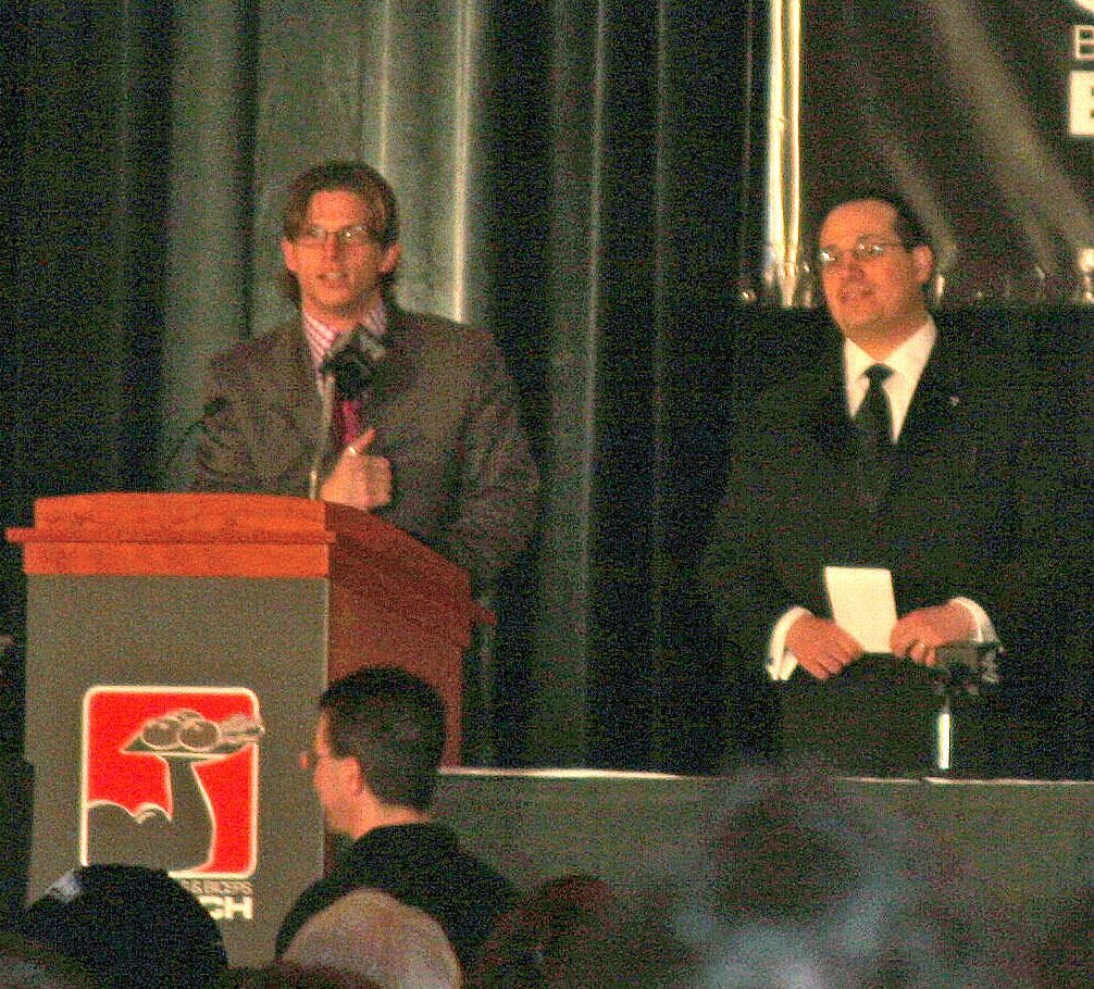 "Josh Mathews, left, along with Joey Styles, welcomes fans to WWE's ""Bacon, Bagels and Biceps"" breakfast prior to WrestleMania 22 in 2006.  (Photo by Mike Pankow)"