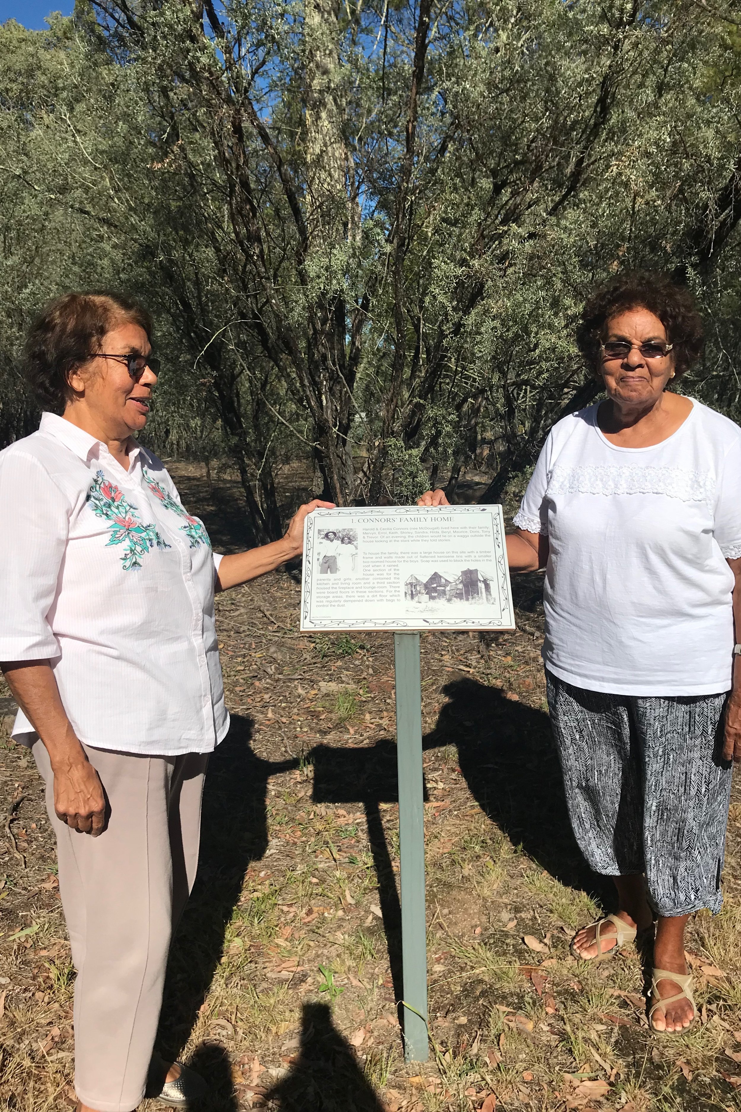 Beryl Hepi and Hilda Dunan at the former Goonoowigall camp and standing next to the site of their childhood house