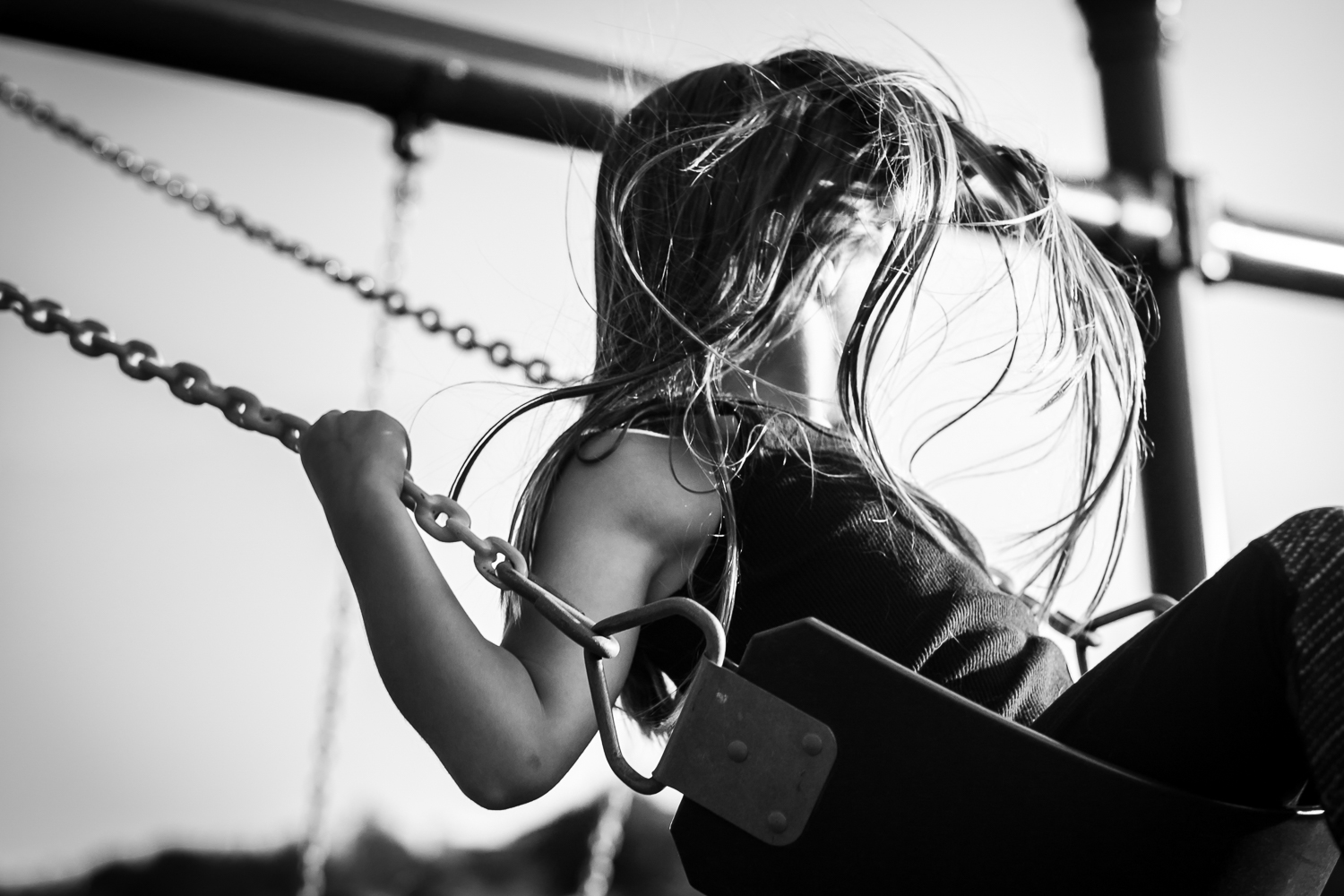 Girl's hair waves in the wind as she swings at the playground during family session in Clermont, Florida.