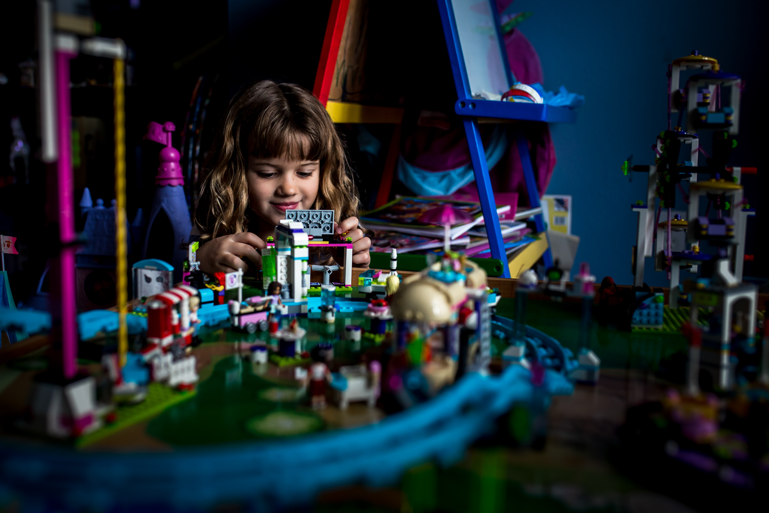 Girl plays with a table full of Legos during family documentary session in Winter Garden, Florida.