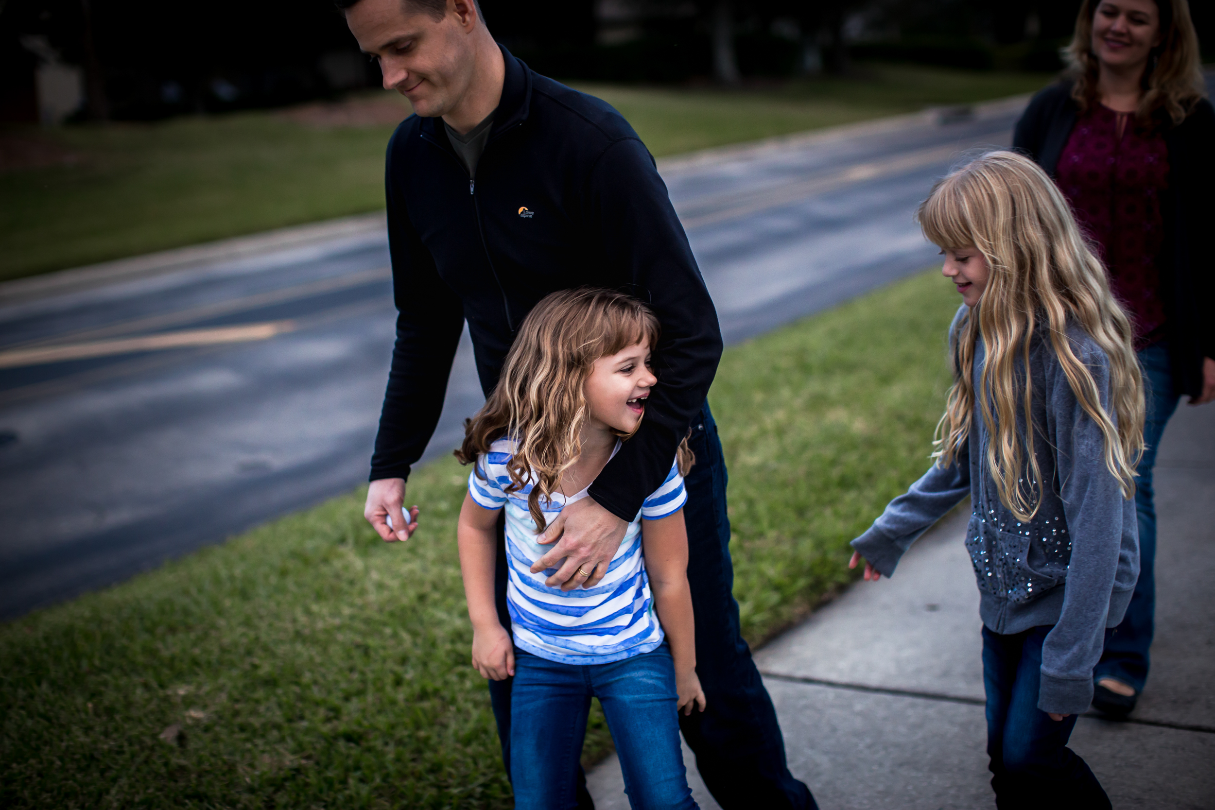 Sisters tease each other during a family walk after dinner during family photography session in Winter Garden, Florida.