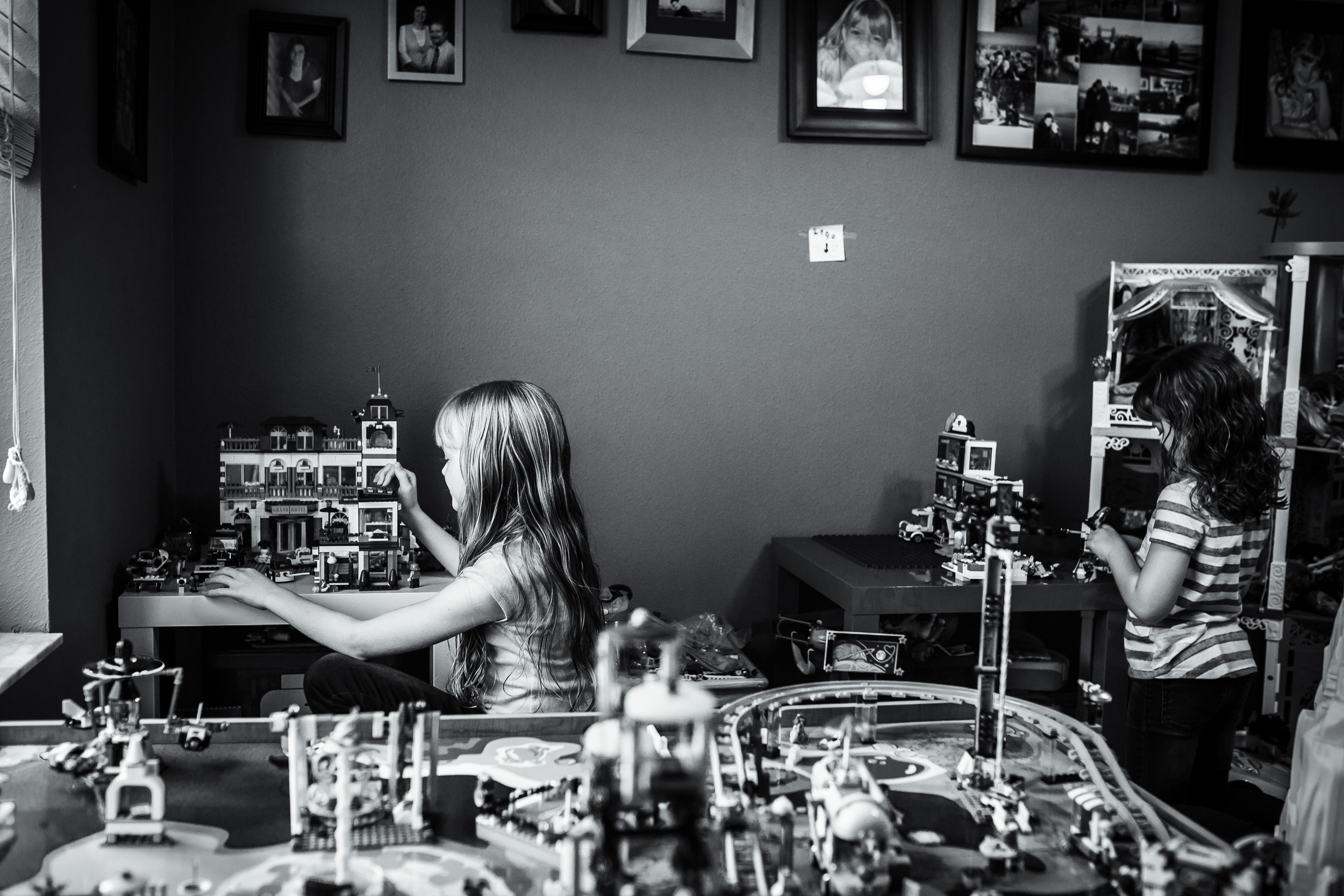 Sisters play Legos during documentary family story photography session in Winter Garden, Florida.