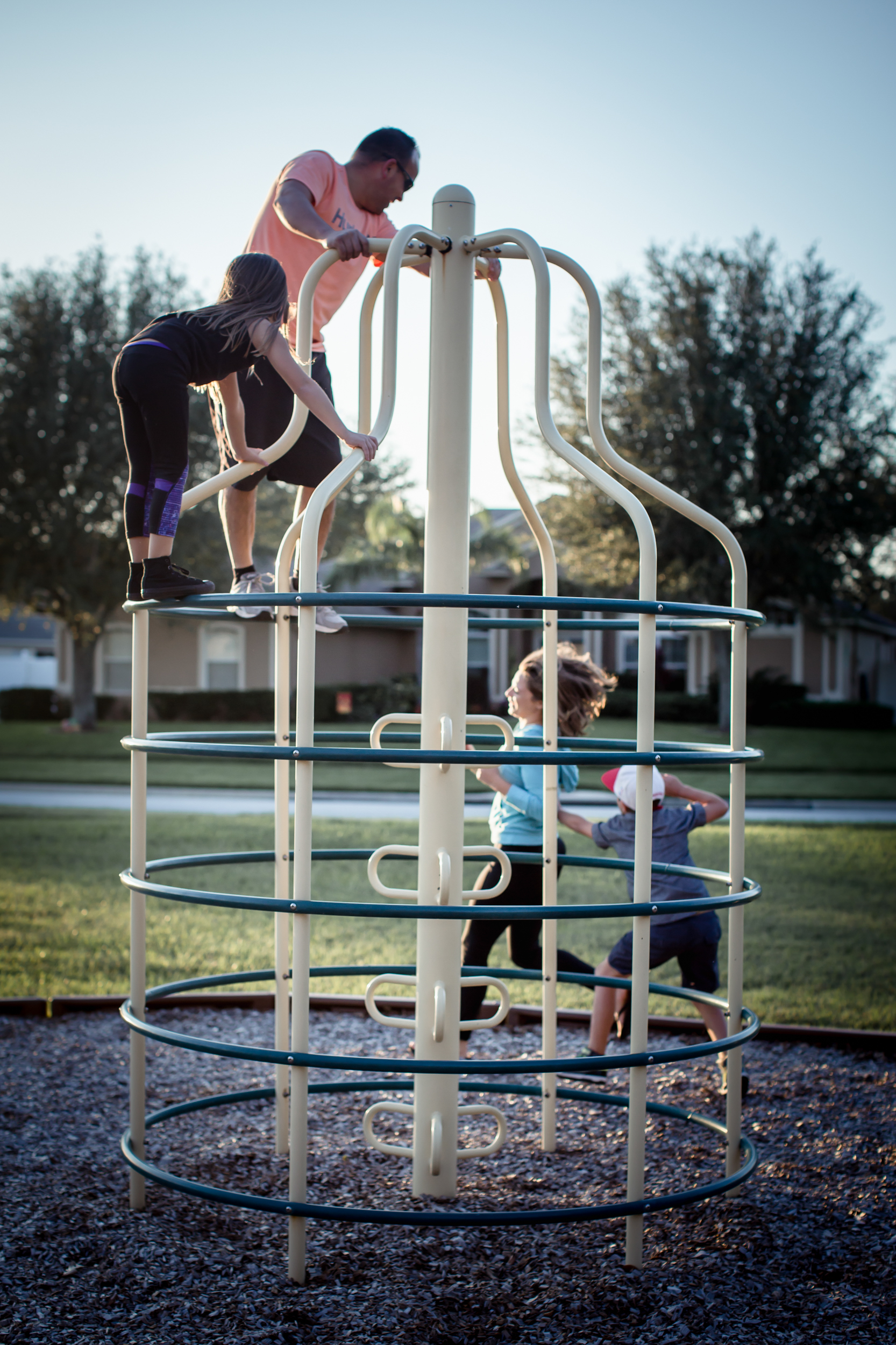 A family of four plays tag at the playground during family story session in Clermont, Florida.