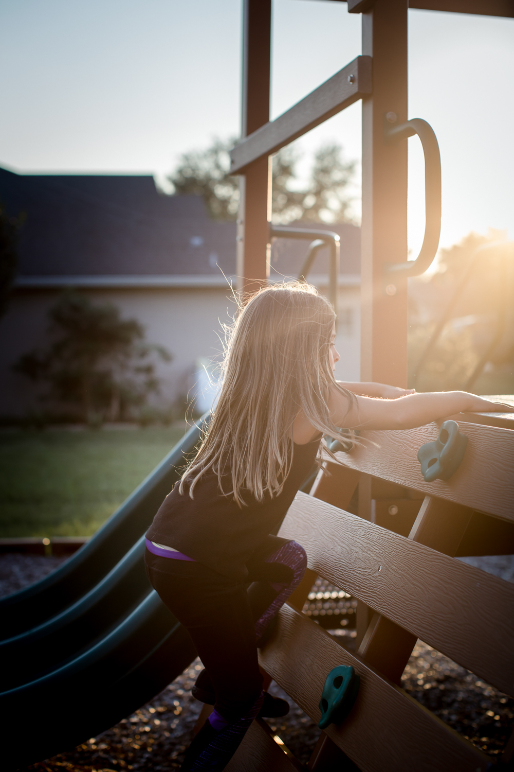 A little girl climbs at the playground in the sunlight during a documentary family story in Clermont, Florida.