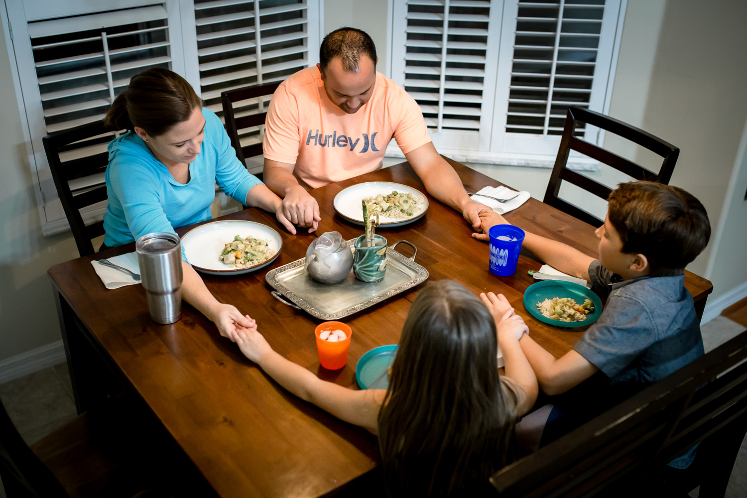 Family says dinner blessing during family photography session in Clermont, Florida.
