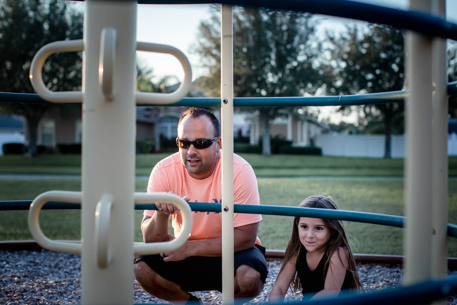 Dad and daughter play hide-and-seek at playground  in Clermont, Florida during family photography session.