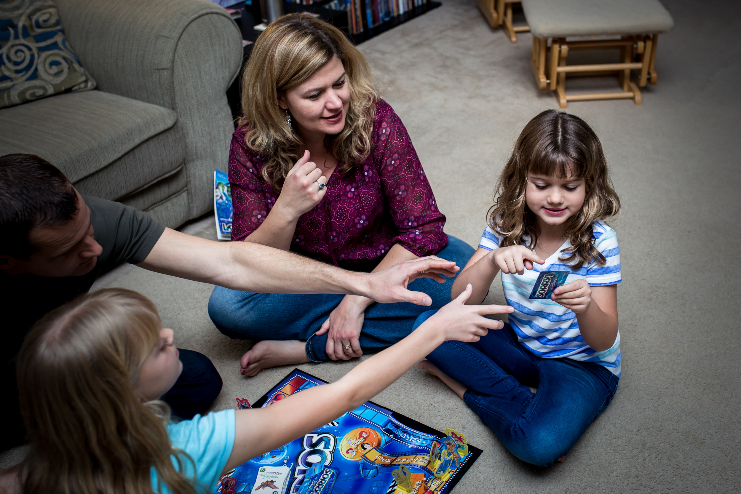 Family plays Sorry during game night for family photography session in Winter Garden, Florida.