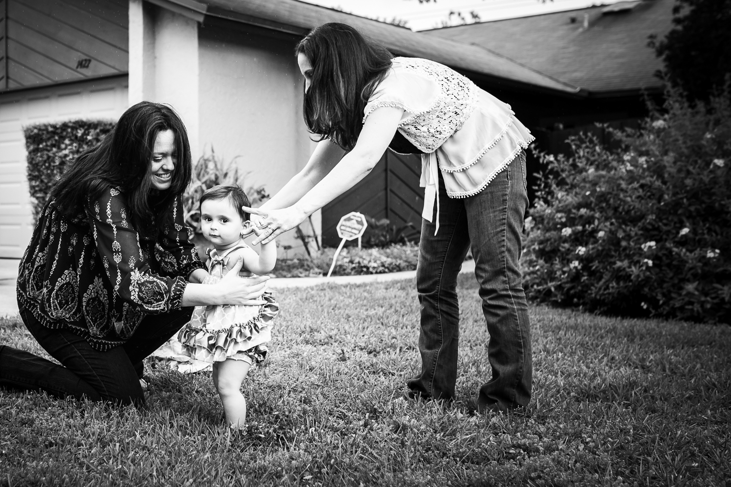 Two moms teach their daughter to walk during milestone session in Oviedo, Florida.