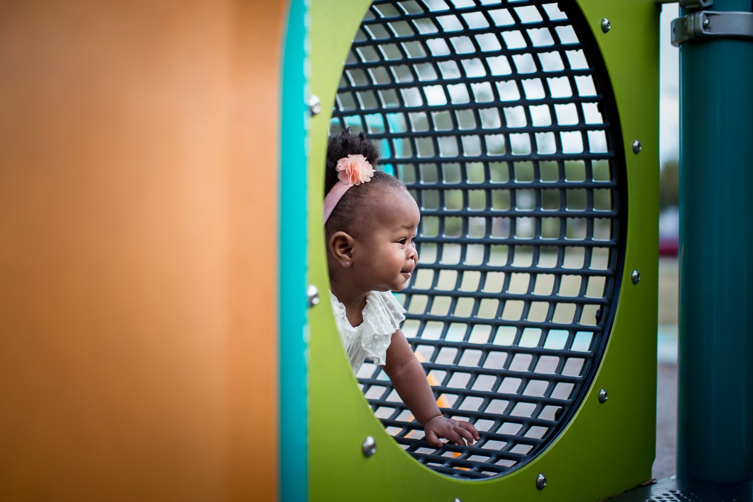 One year old plays on the playground during milestone session in Orlando, Florida.