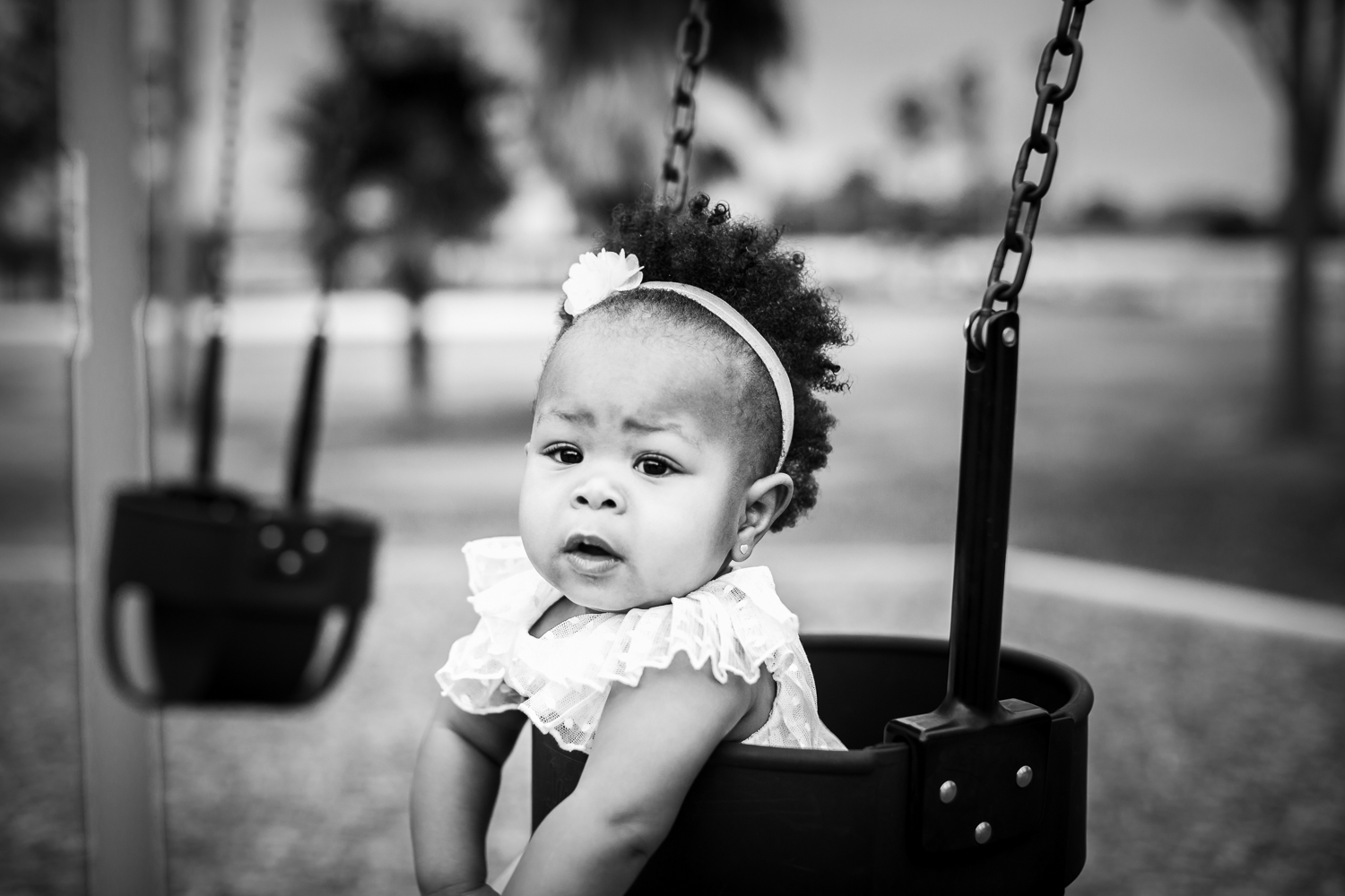 Little girl swings at playground during one year old session in Orlando, Florida.