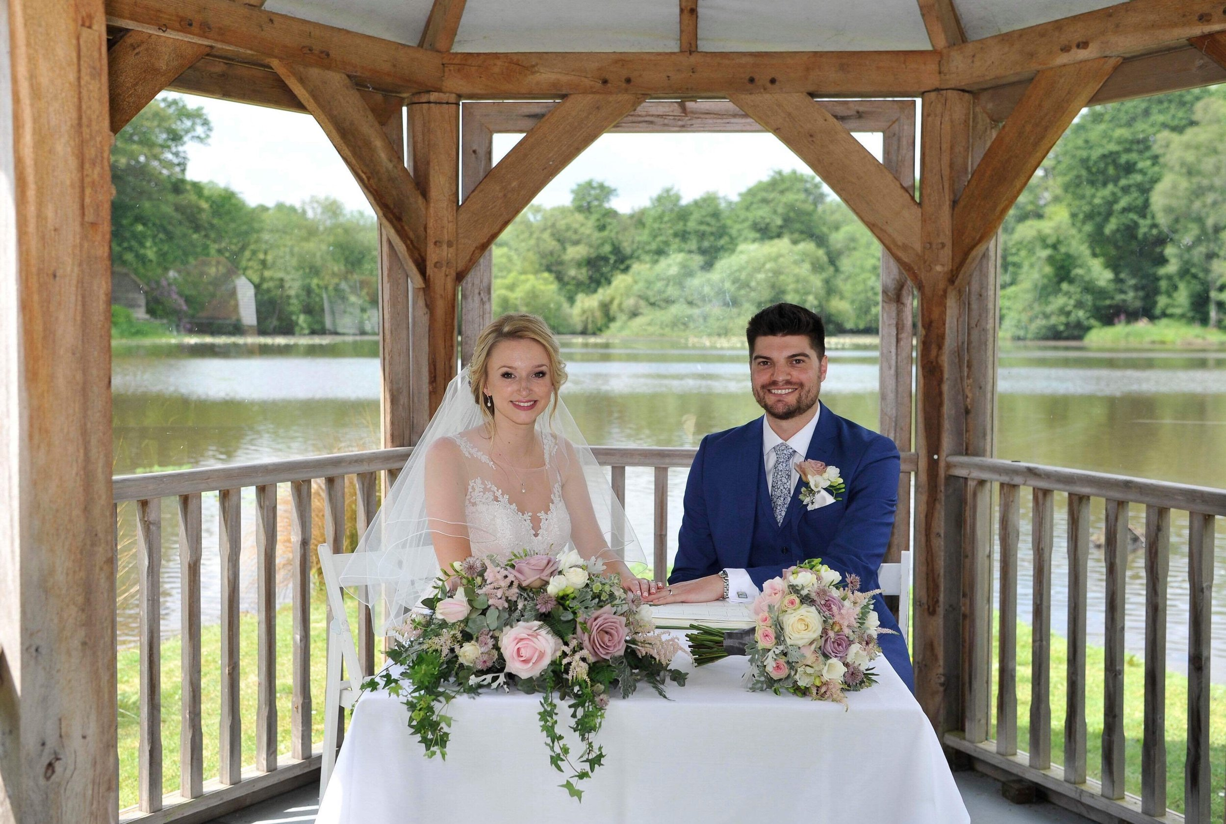 Bride and groom with wedding flowers in Sussex.