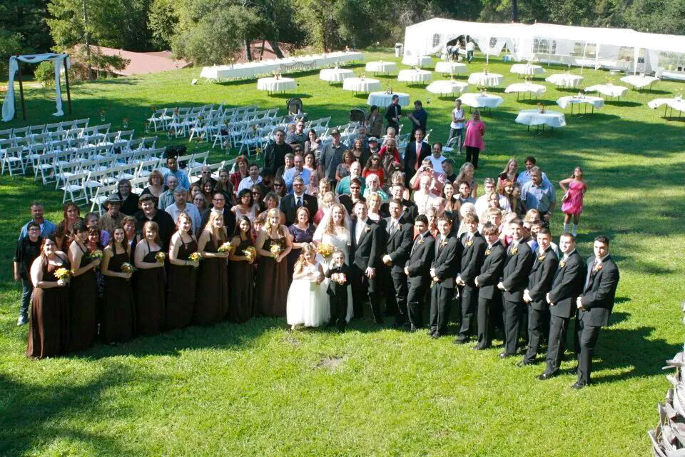 The wedding party poses for a picture on the sunny green lawn of Indian Creek Inn in Anderson Valley, CA