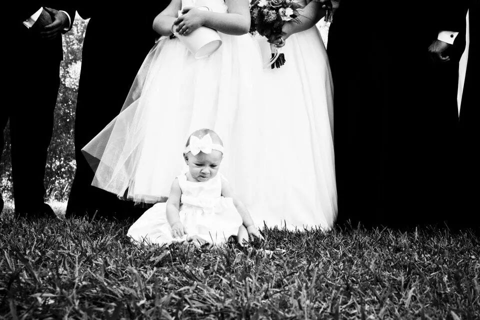 A baby dressed up for the wedding sits on the lawn at Indian Creek Inn in Anderson Valley, CA