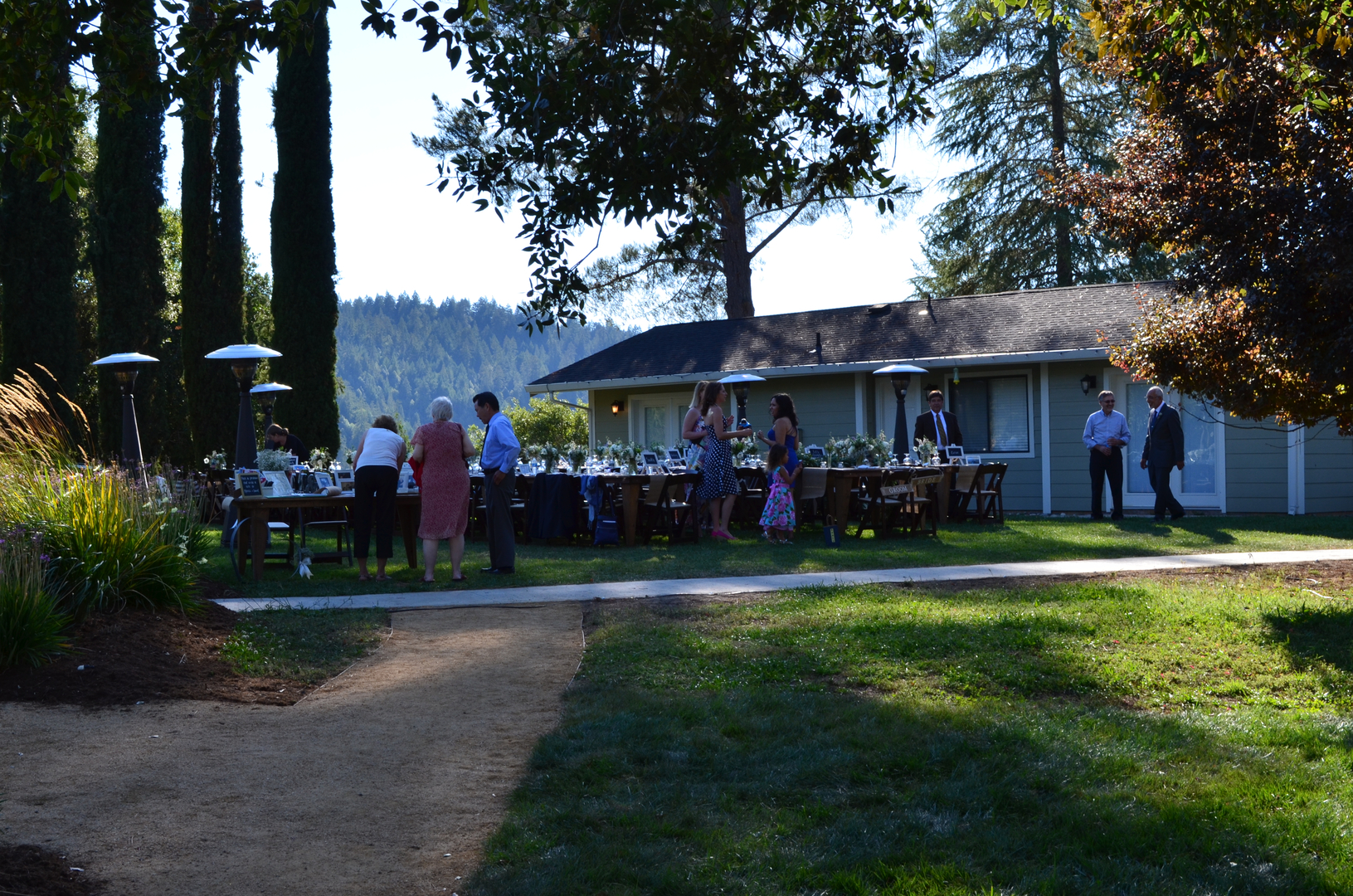 Wedding guests gather around the outdoor tables on a sunny day at Indian Creek Inn in Anderson Valley, CA