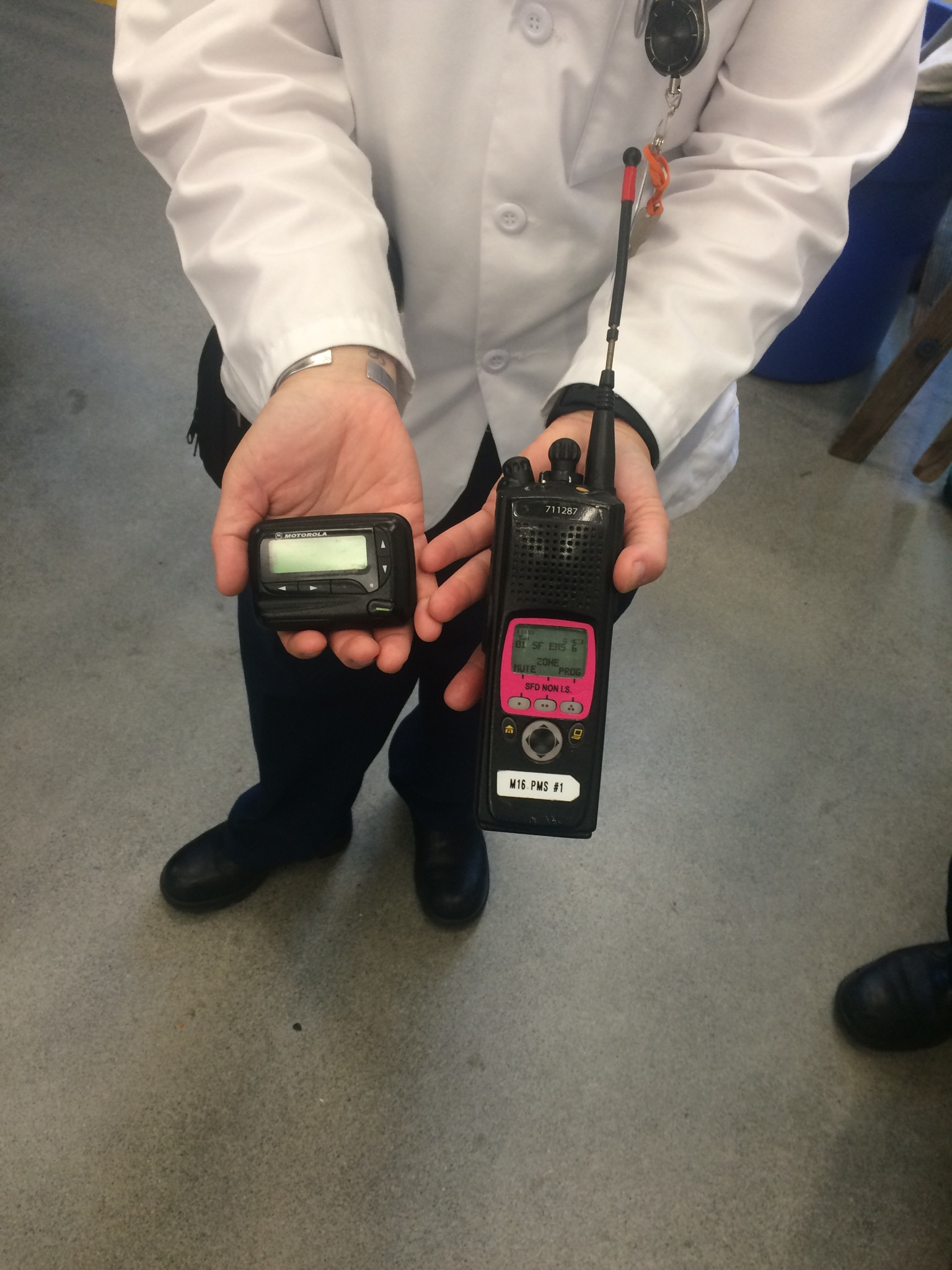 A paramedic showing us her radio and pager. - We listened in on a call over the radio channel and it was a muffled paramedic's voice describing the injury to a doctor so he could prep before the patient came in.