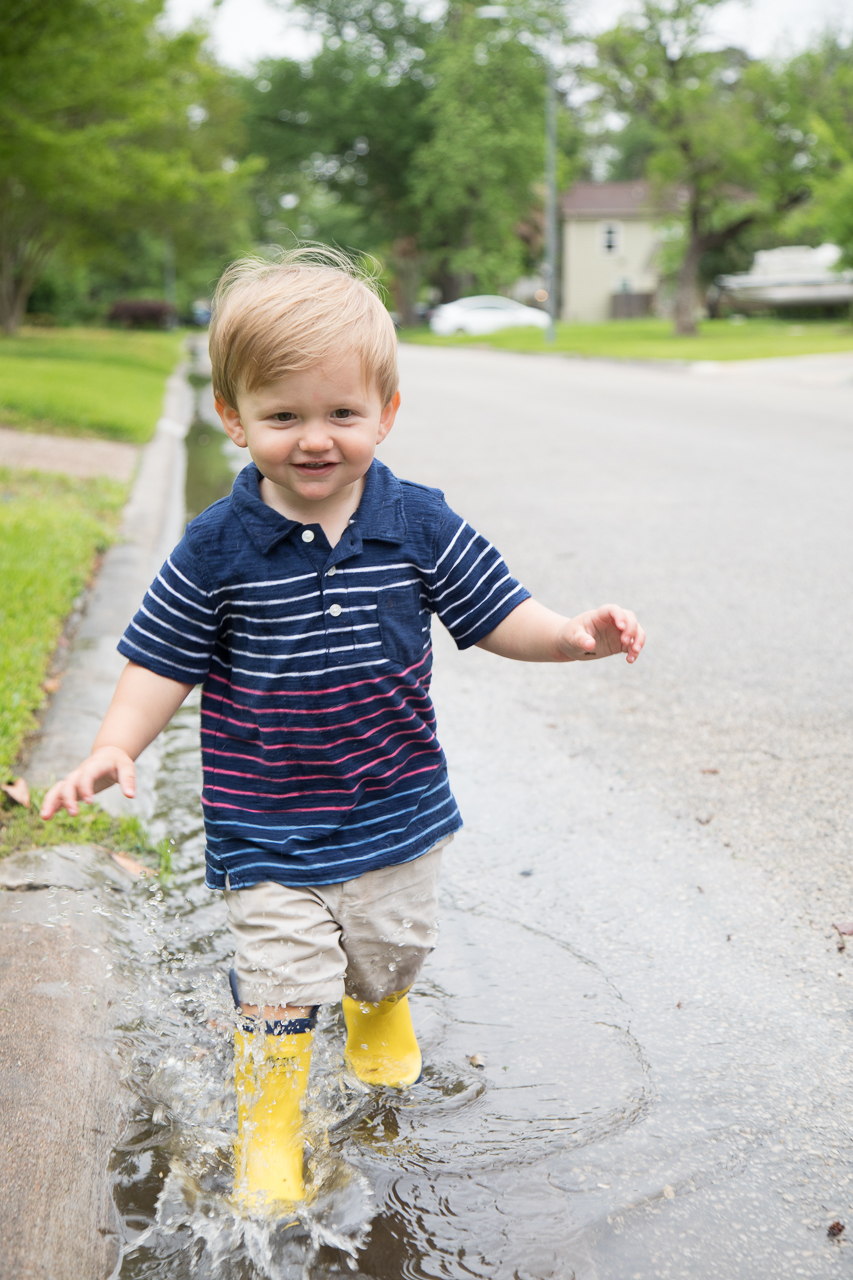 houston family documentary photography boy splashing in rain puddles with yellow rain boots