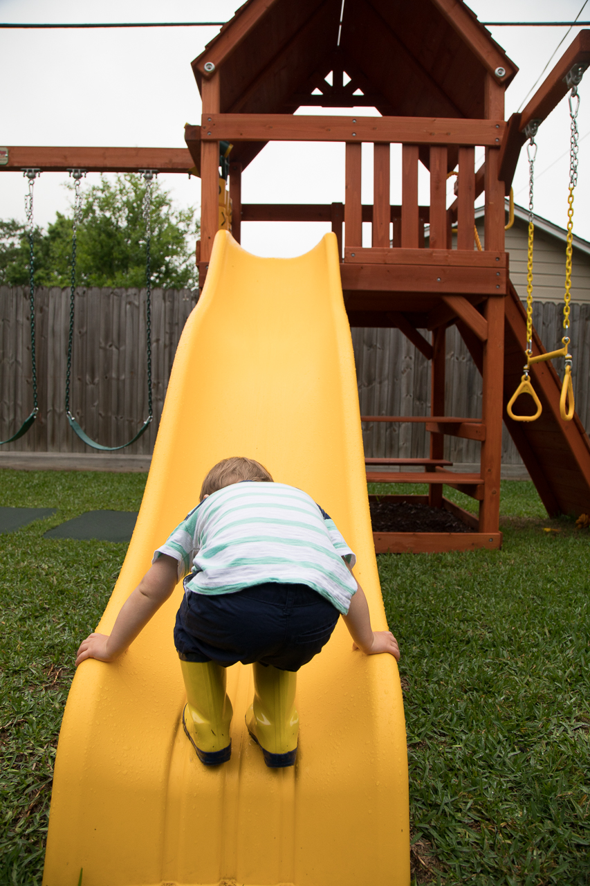 houston family documentary photography boy climbing up yellow slide wearing yellow rain boots