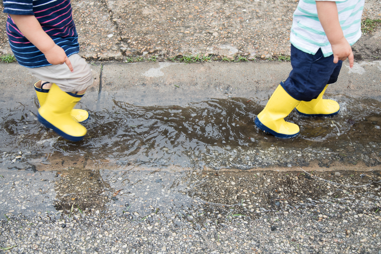 houston family documentary photography boys splashing in puddles with yellow rainboots