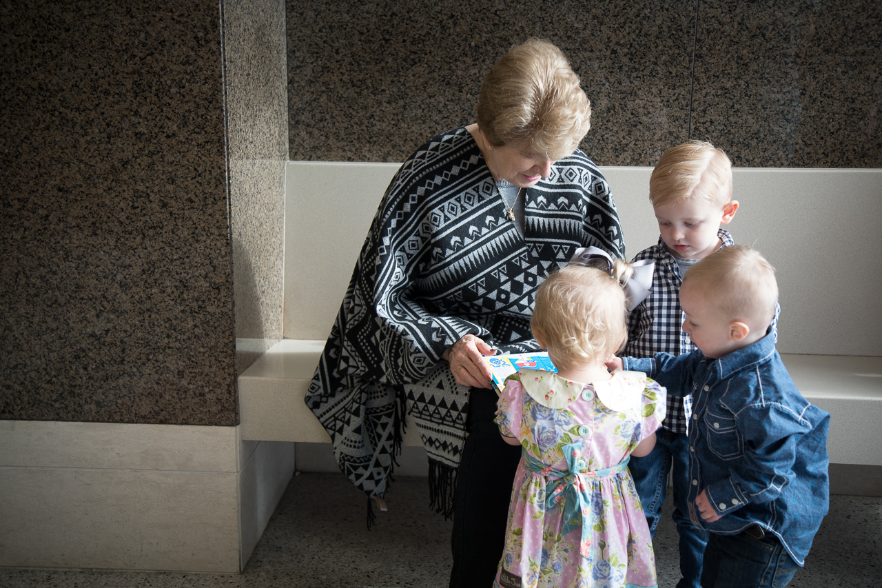 adoption photography grandmother reading to grandchildren outside courtroom