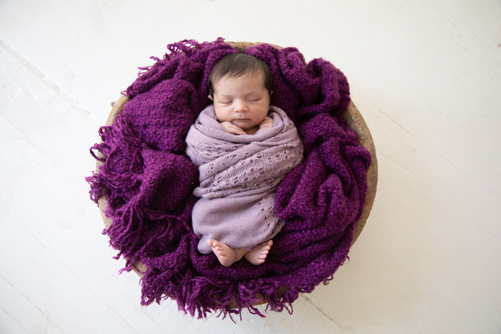Houston newborn photography baby in teak bowl with purple blanket