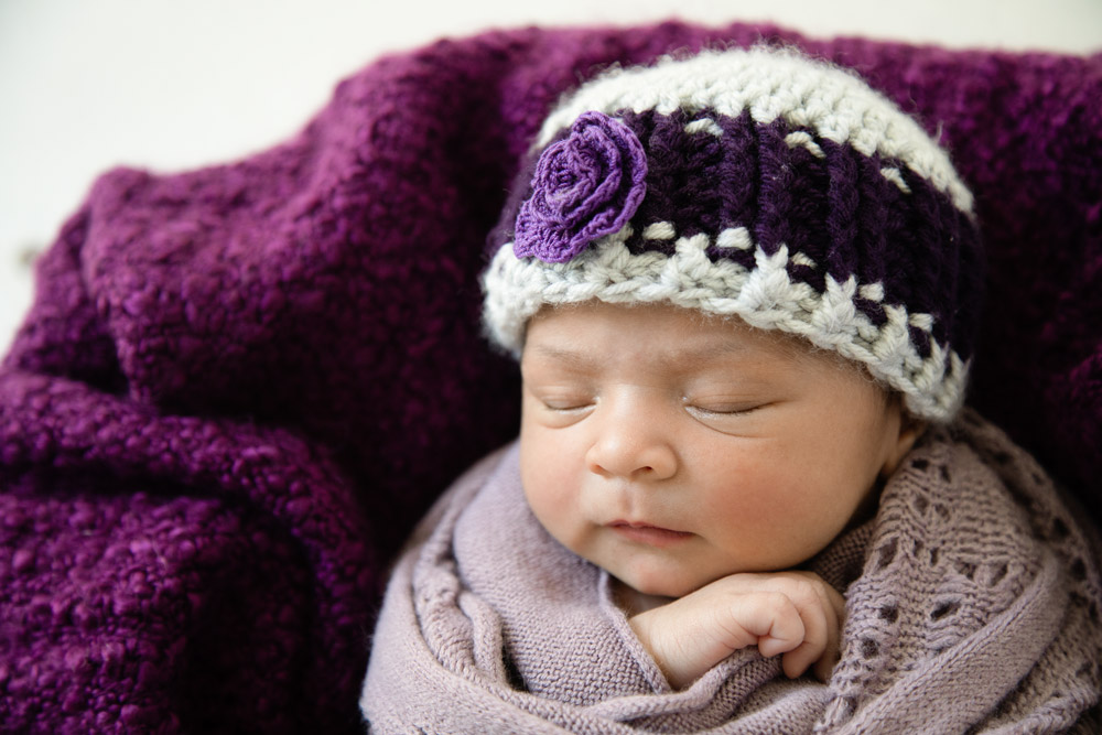 Houston newborn photography sleeping baby in teak bowl with purple hat