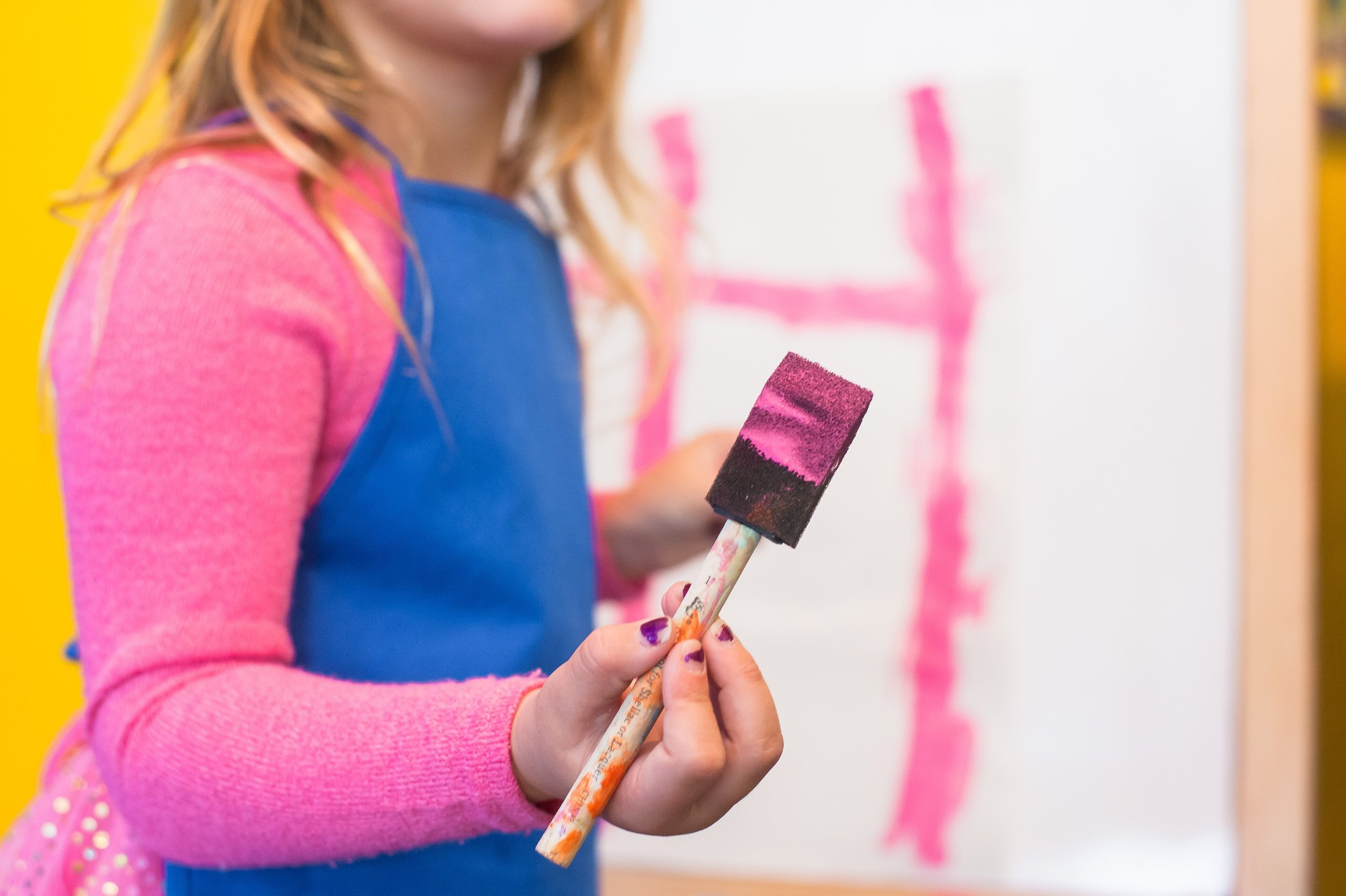 Child girl doing art therapy painting pink