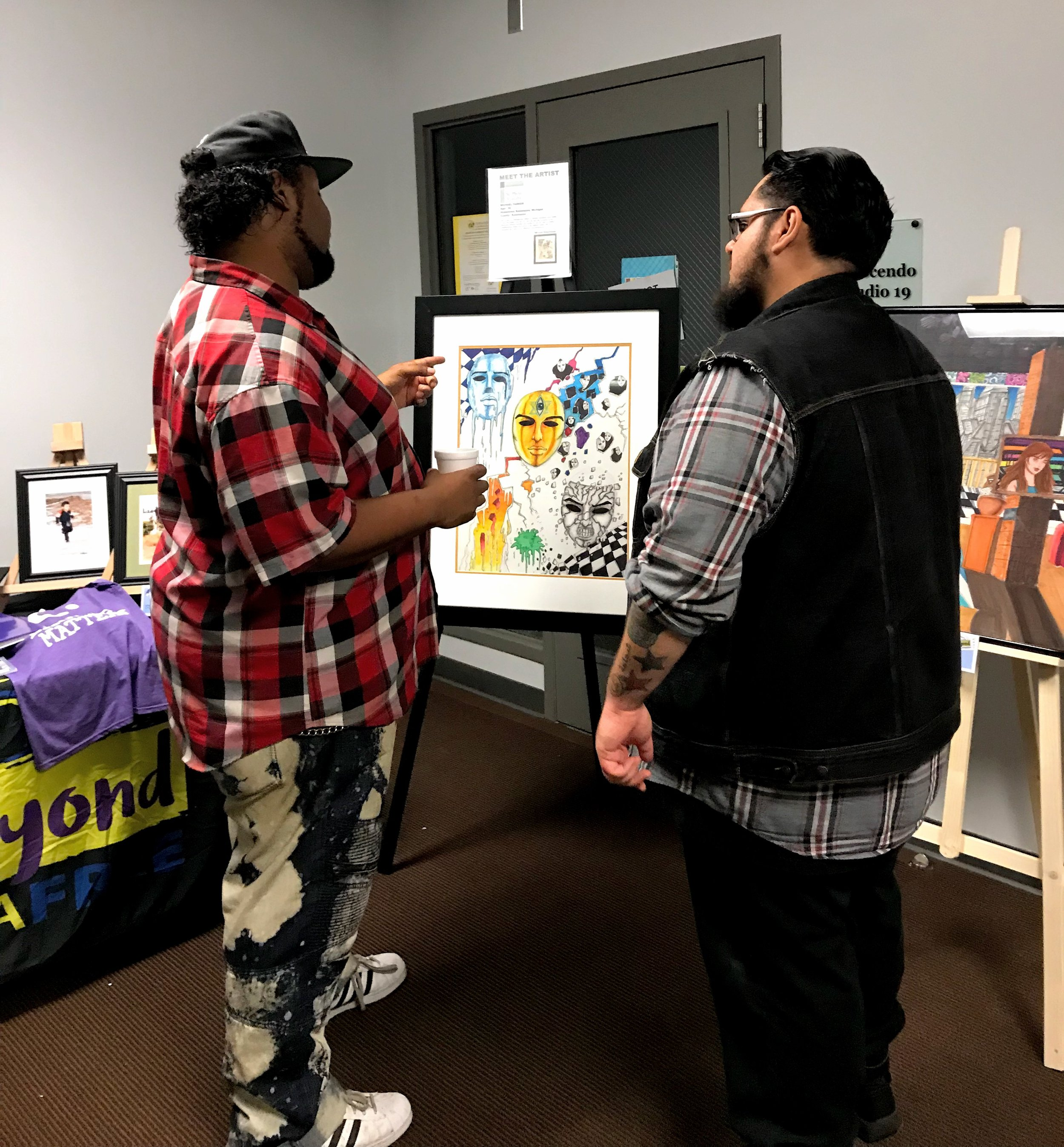 Michael (left) discusses his painting at our 2018 Art Hop event.